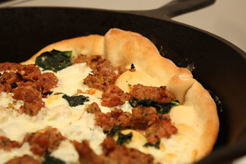 pizza cooked in a heated cast iron skillet
