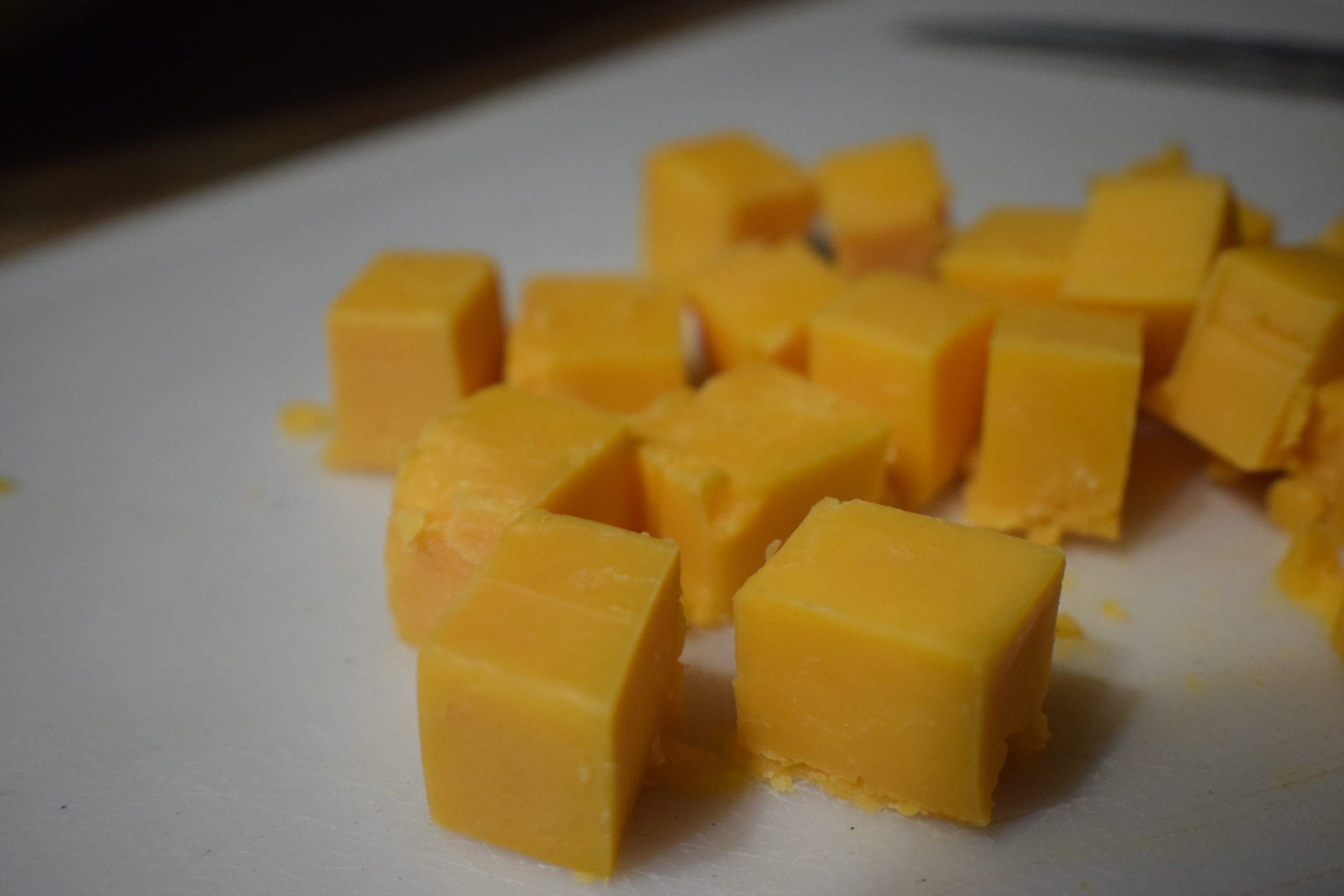Cheddar cheese cubes on white plate
