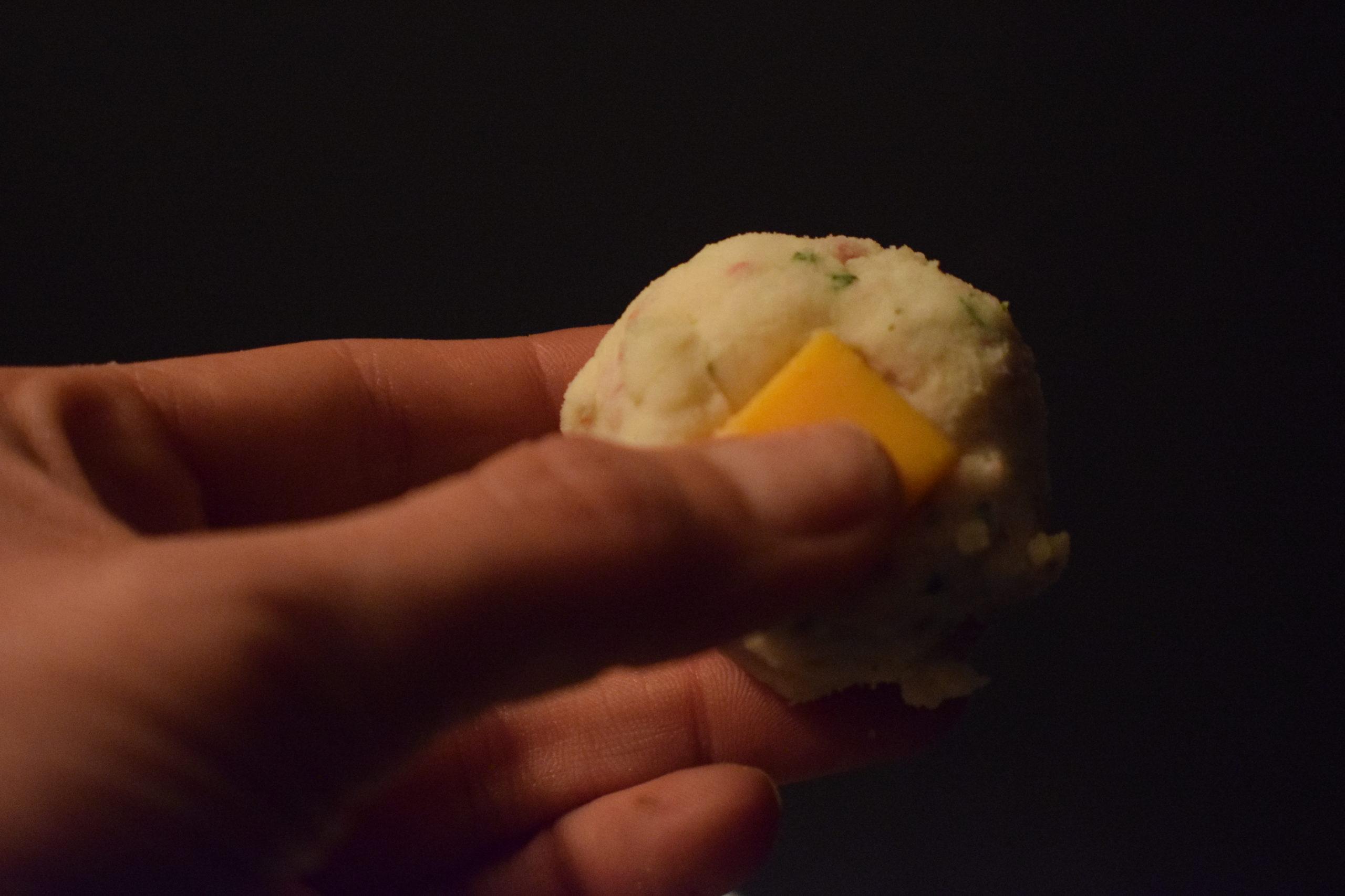 Thumb pushing cheddar cheese into mashed potato ball