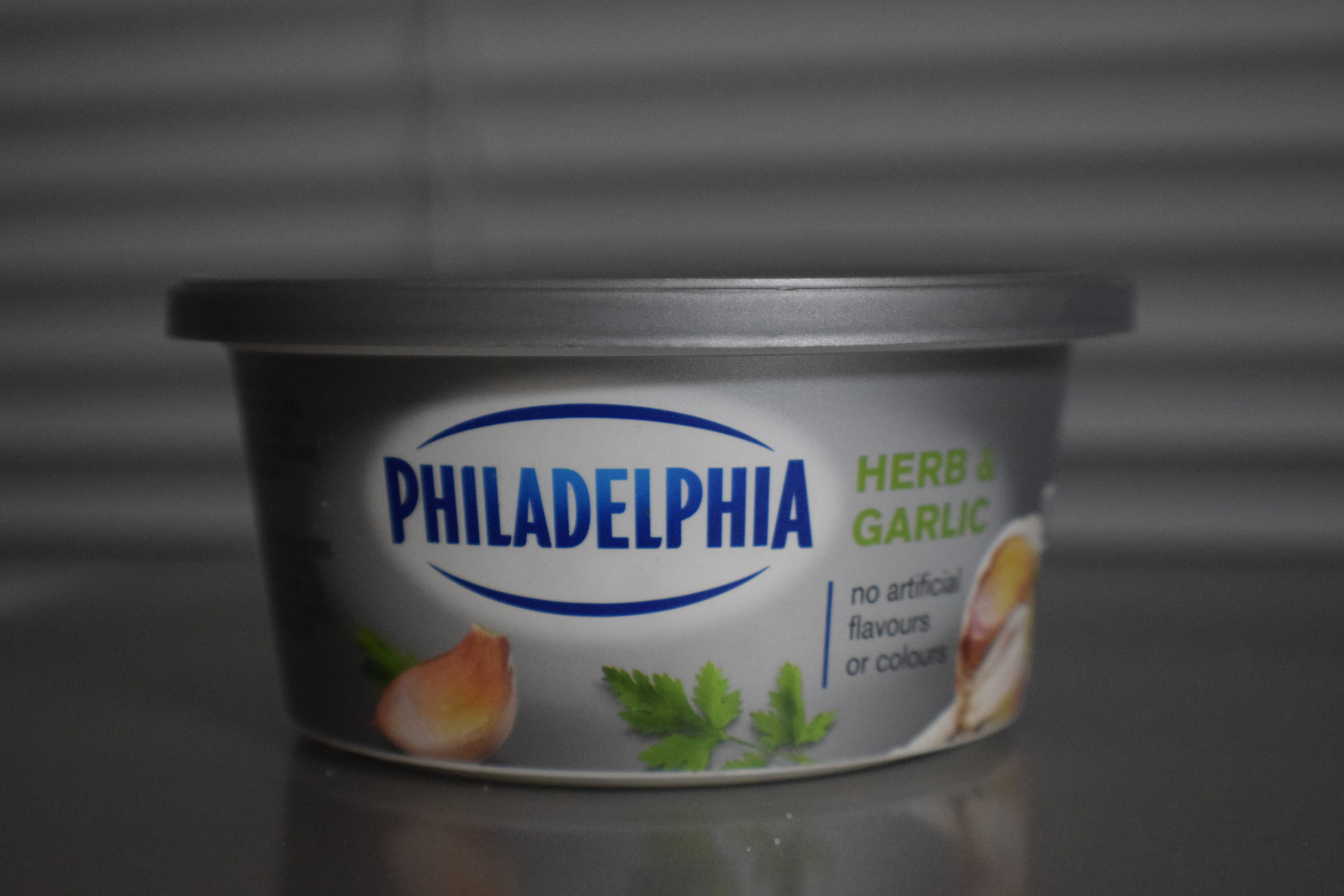 herb and garlic philadelphia cream cheese in front of blinds