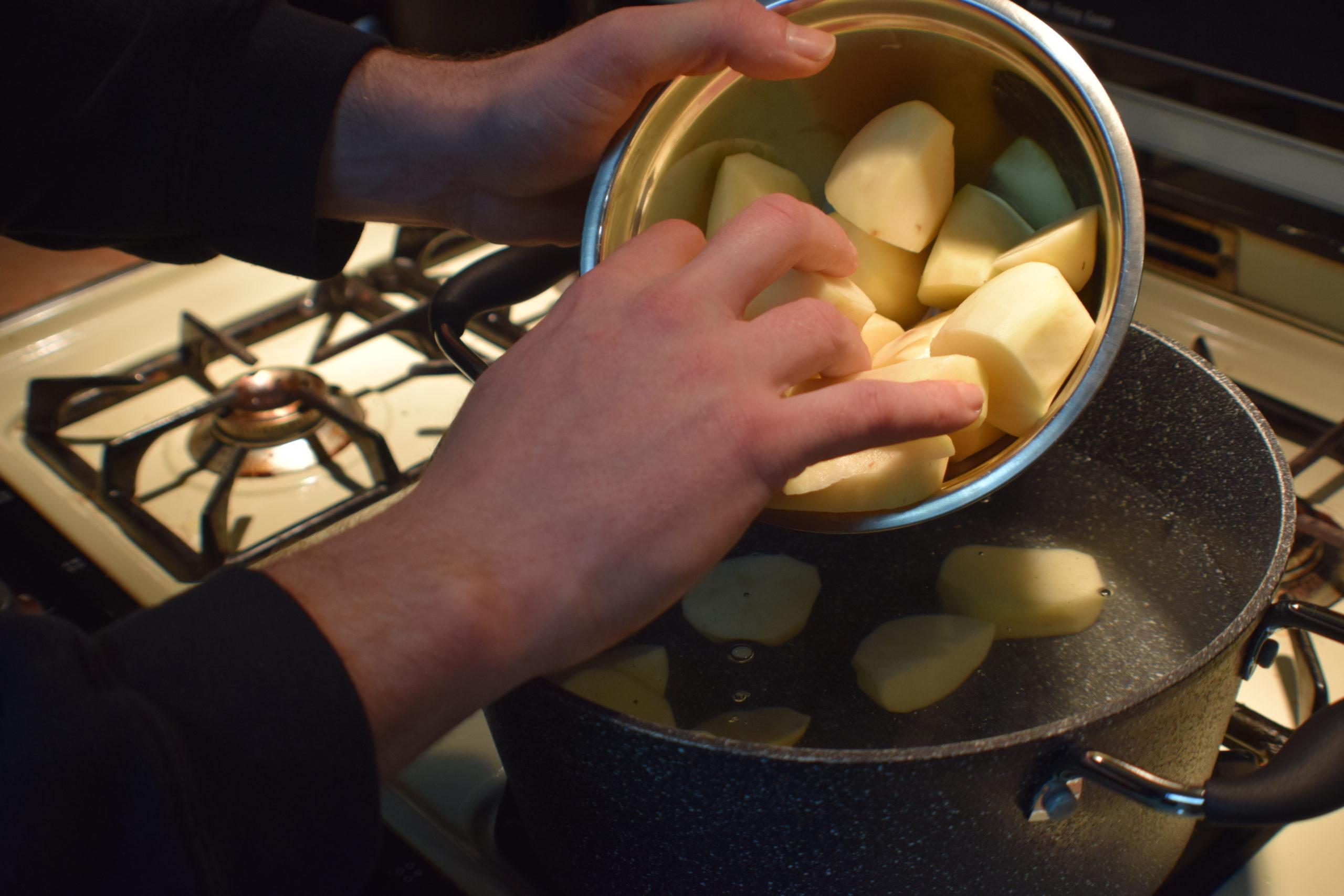 mans hands putting cut potatoes into a pot of water