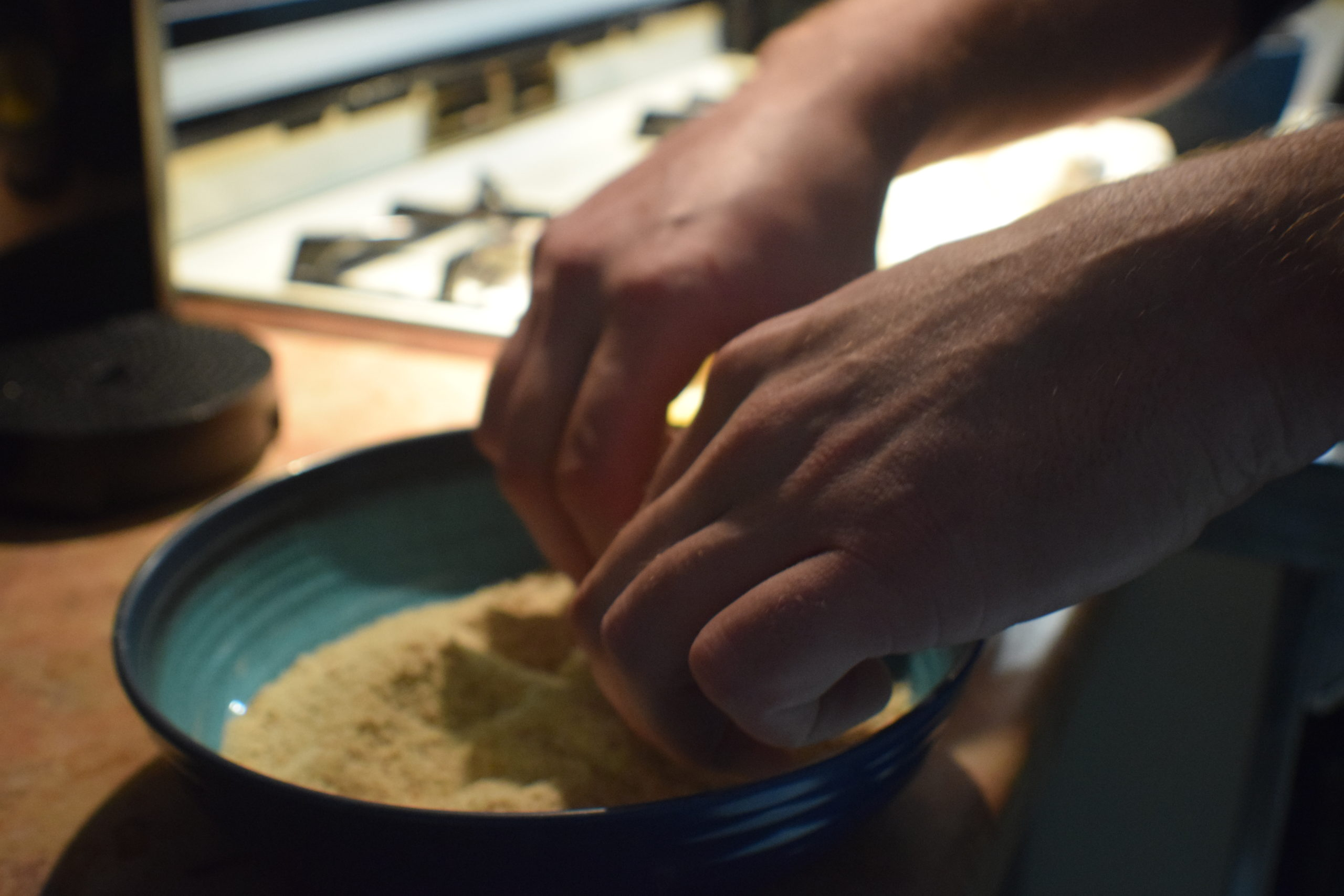 Man hands rolling food into breadcrumbs in a blue bowl