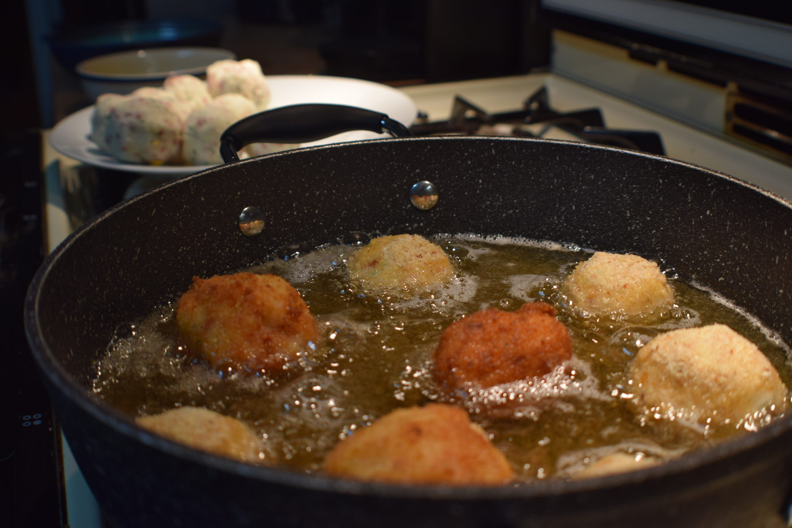 breaded potato balls cooking in hot oil on the stove