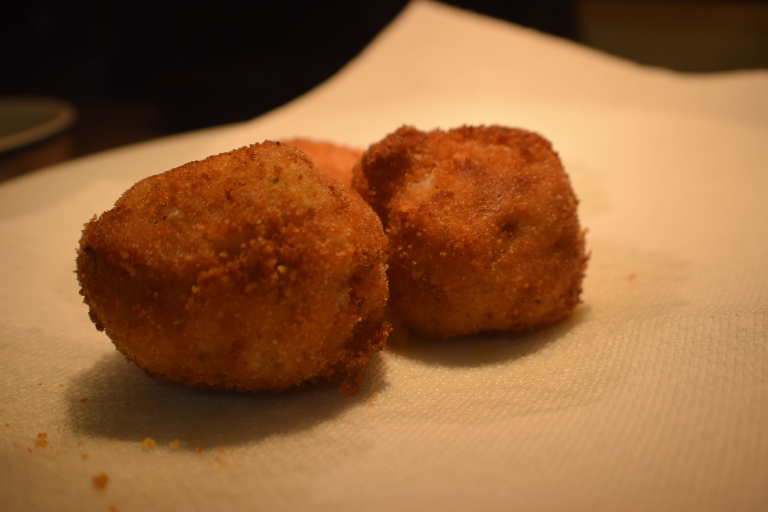 breaded potato balls on paper towel catching grease