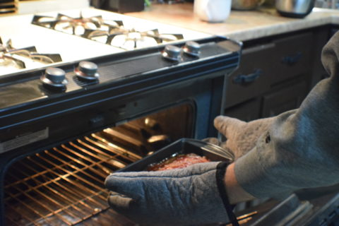 Man with grey striped oven mitts removing meatloaf from oven