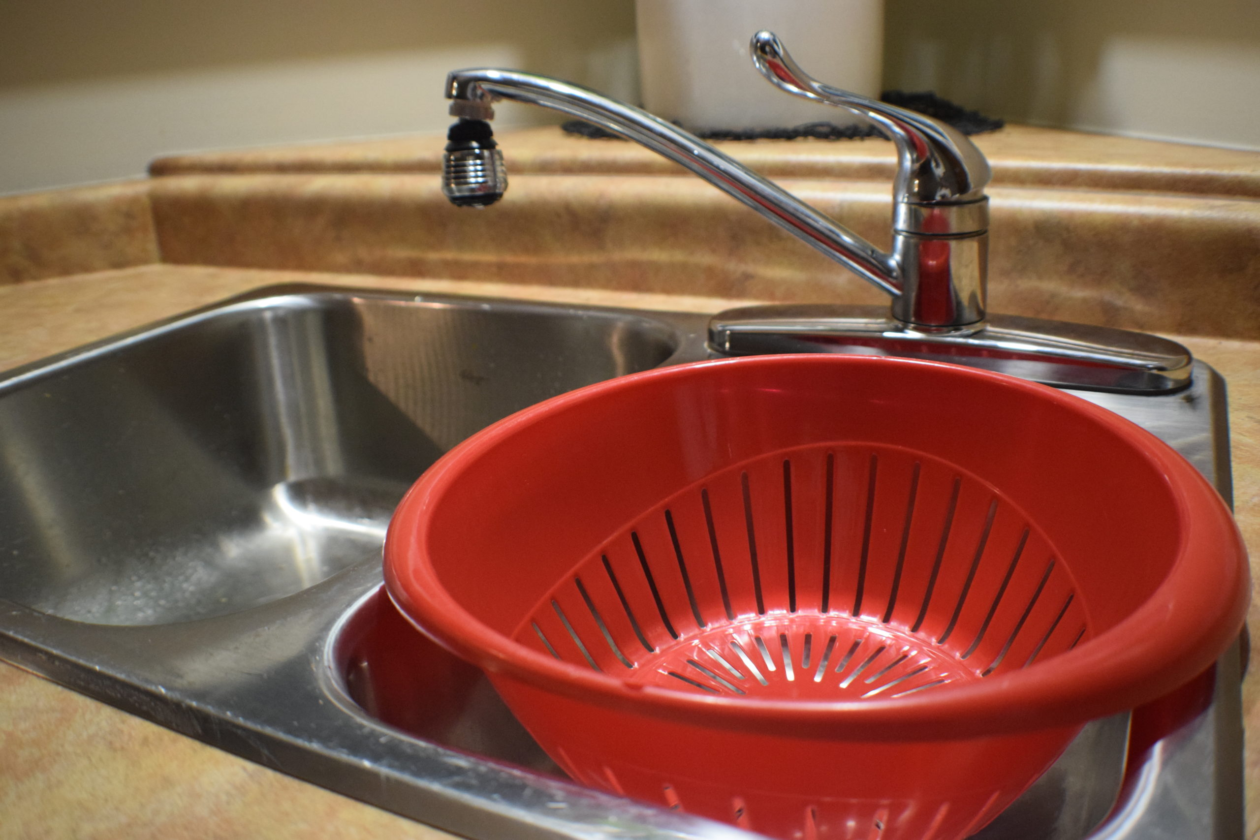 red strainer in small side of sink