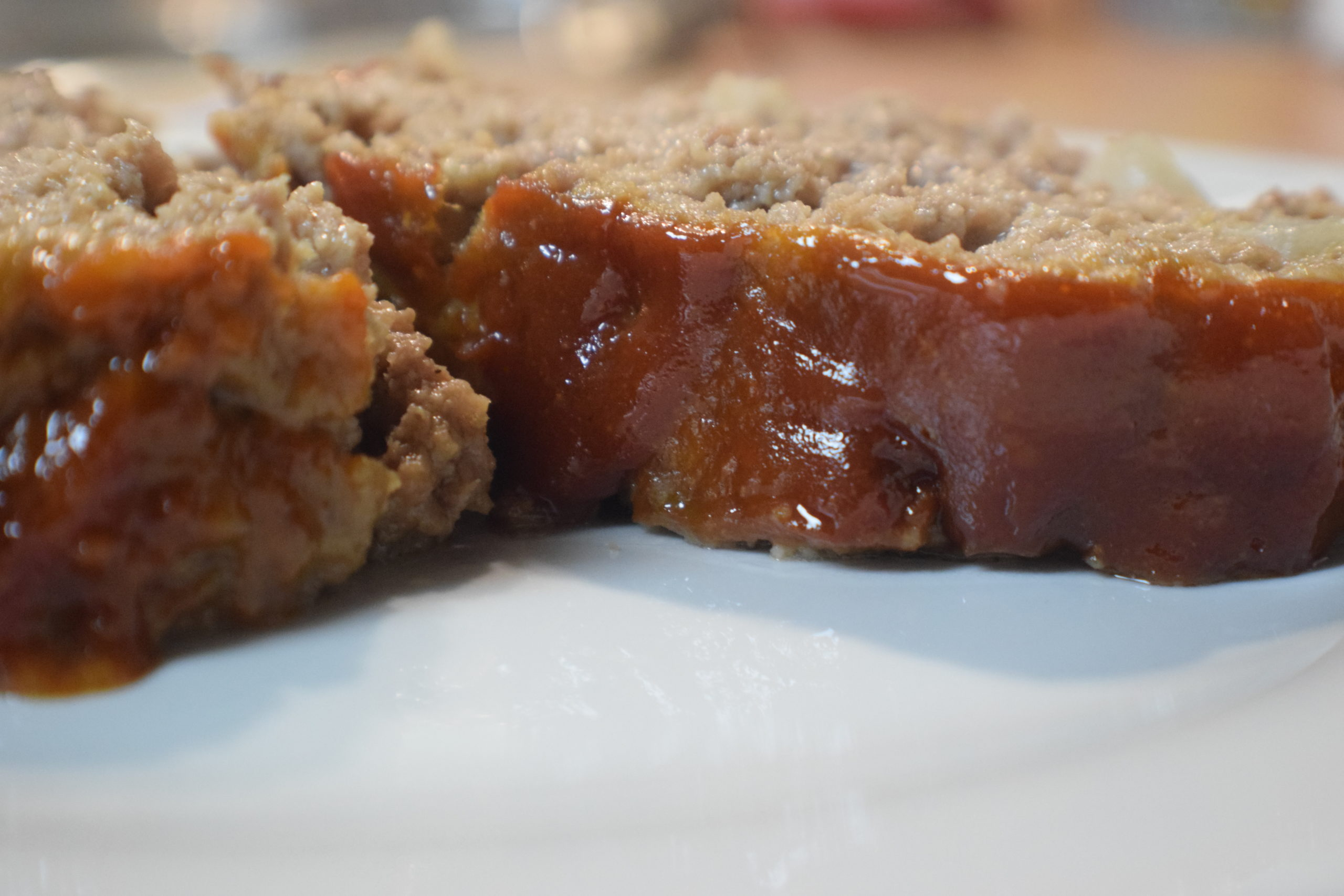 two pieces of meatloaf with red sauce on white plate