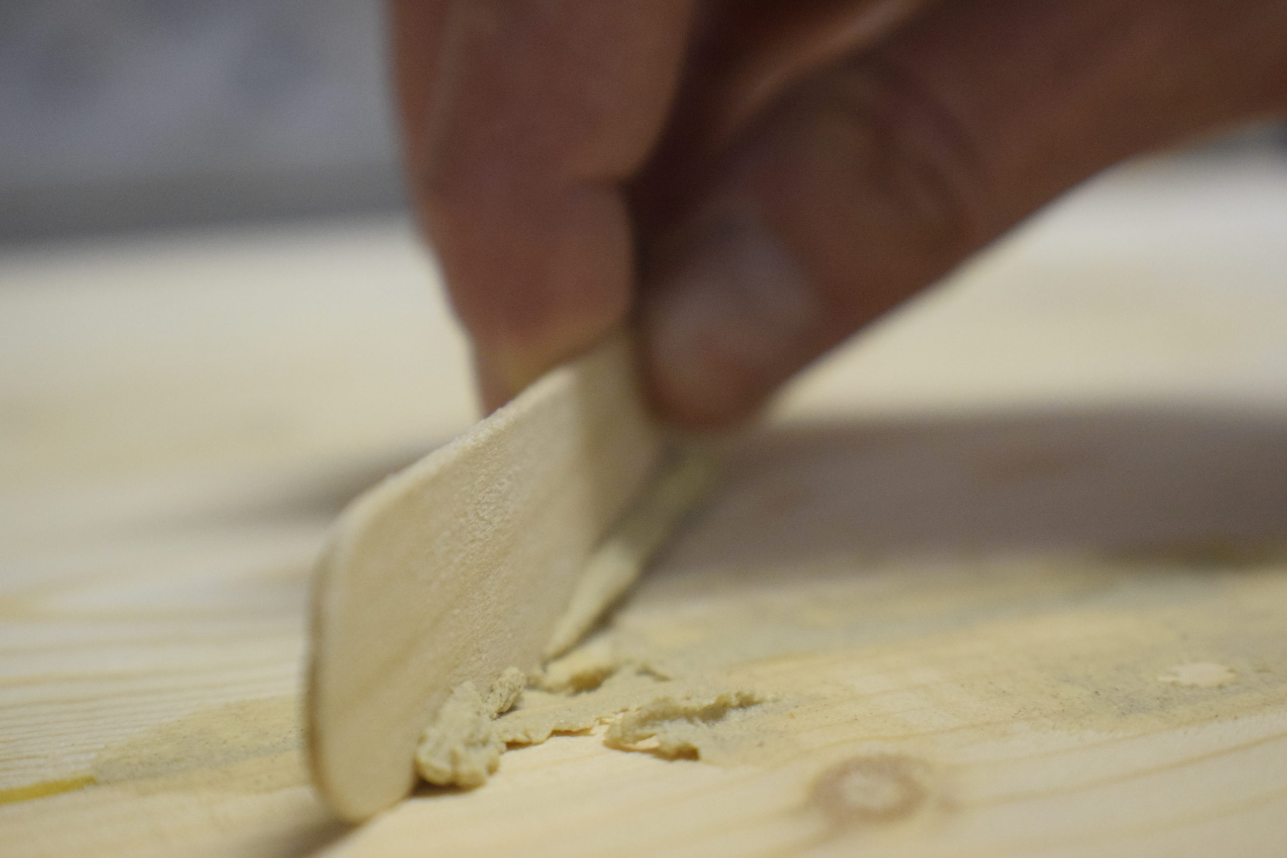 hand using popsicle stick to wipe away excess wood filler on pine wood