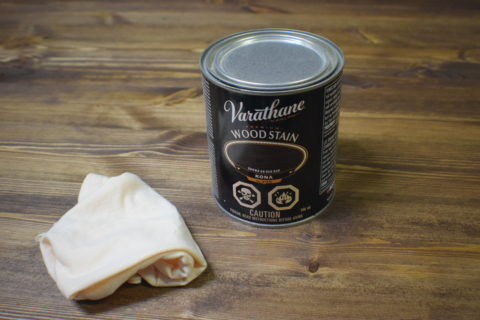 can of varathane premium wood stain with black label on wood table with rag