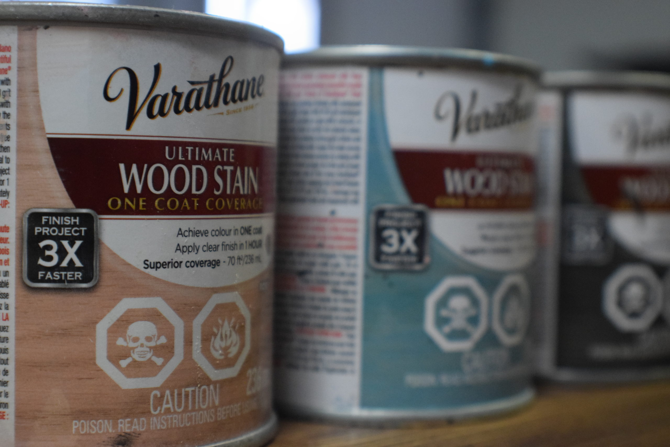 Varathane wood stain cans in pink, aqua and charcoal lined up on a table