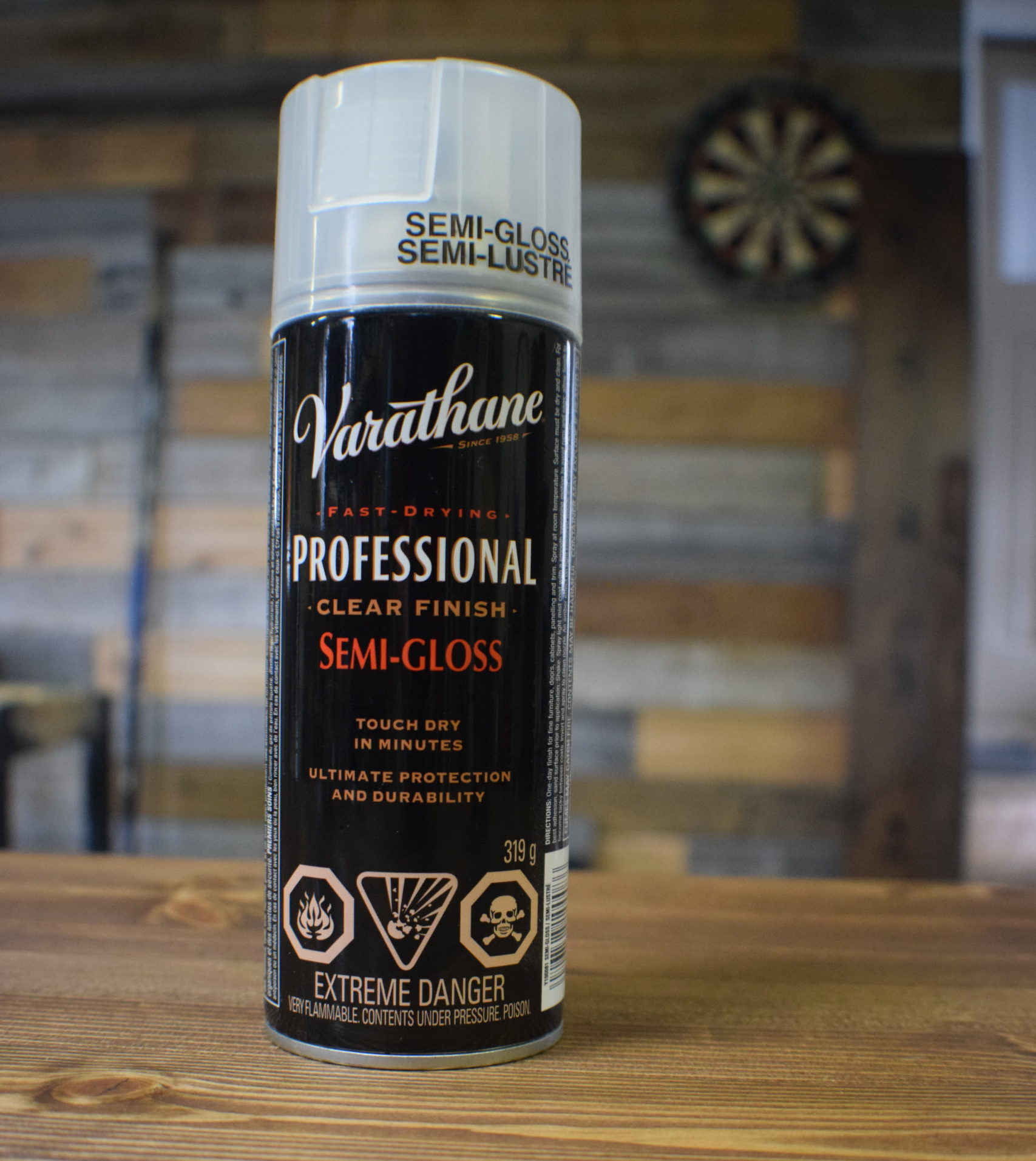 Spray can of varathane professional clear finish semi gloss with white and red text on wood background