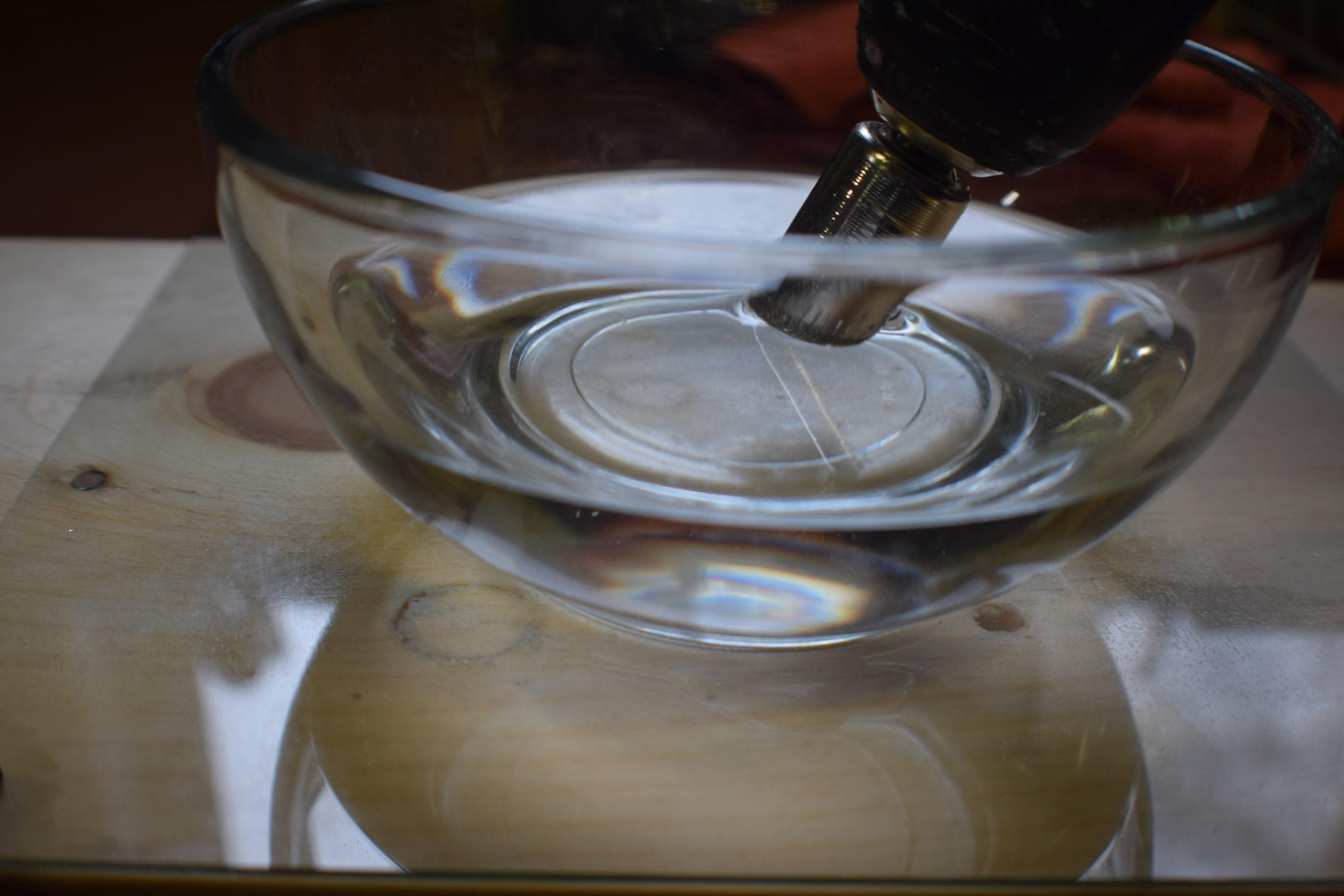 rinsing diamond drill bit in a dish of water