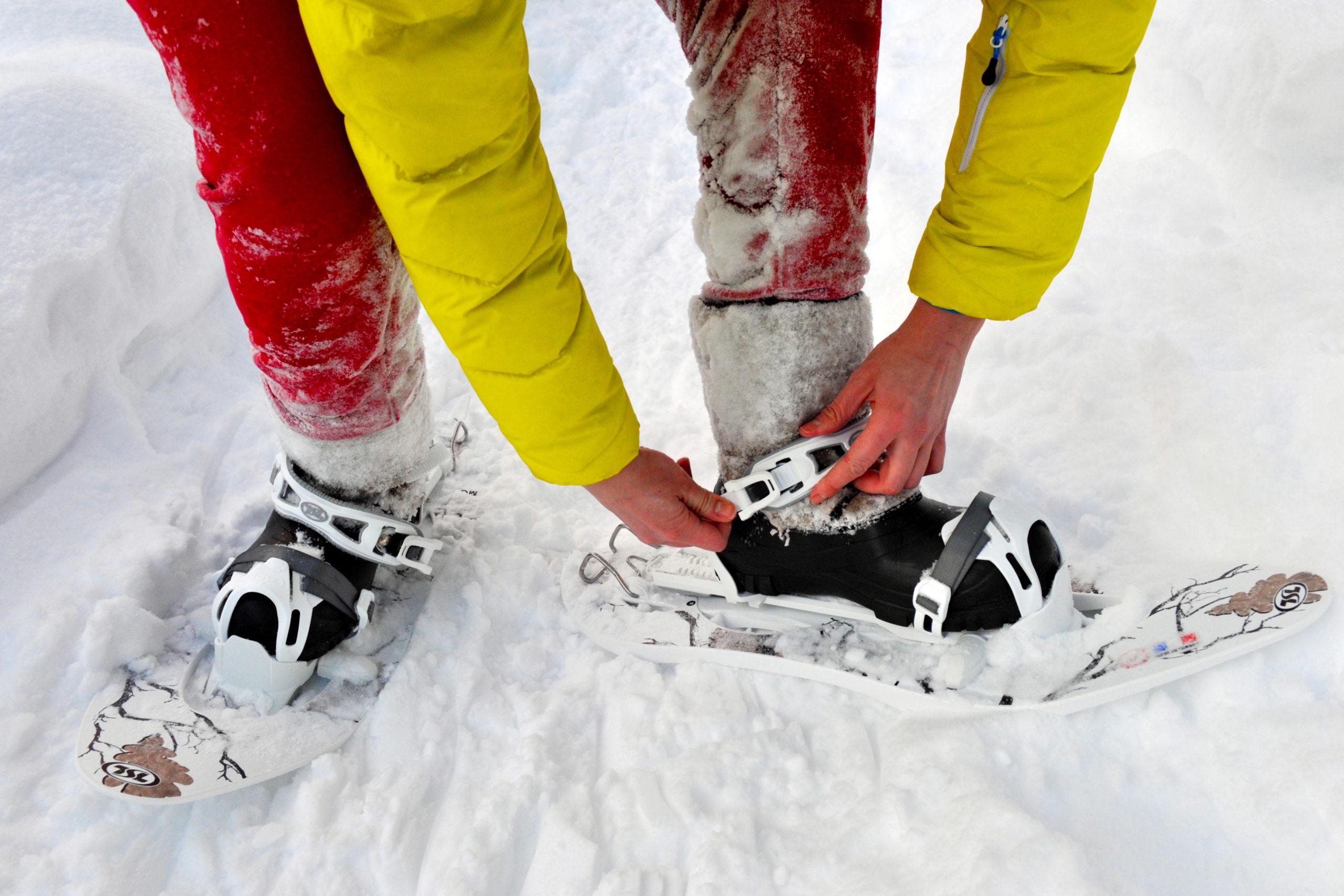 tourist puts on snowshoes