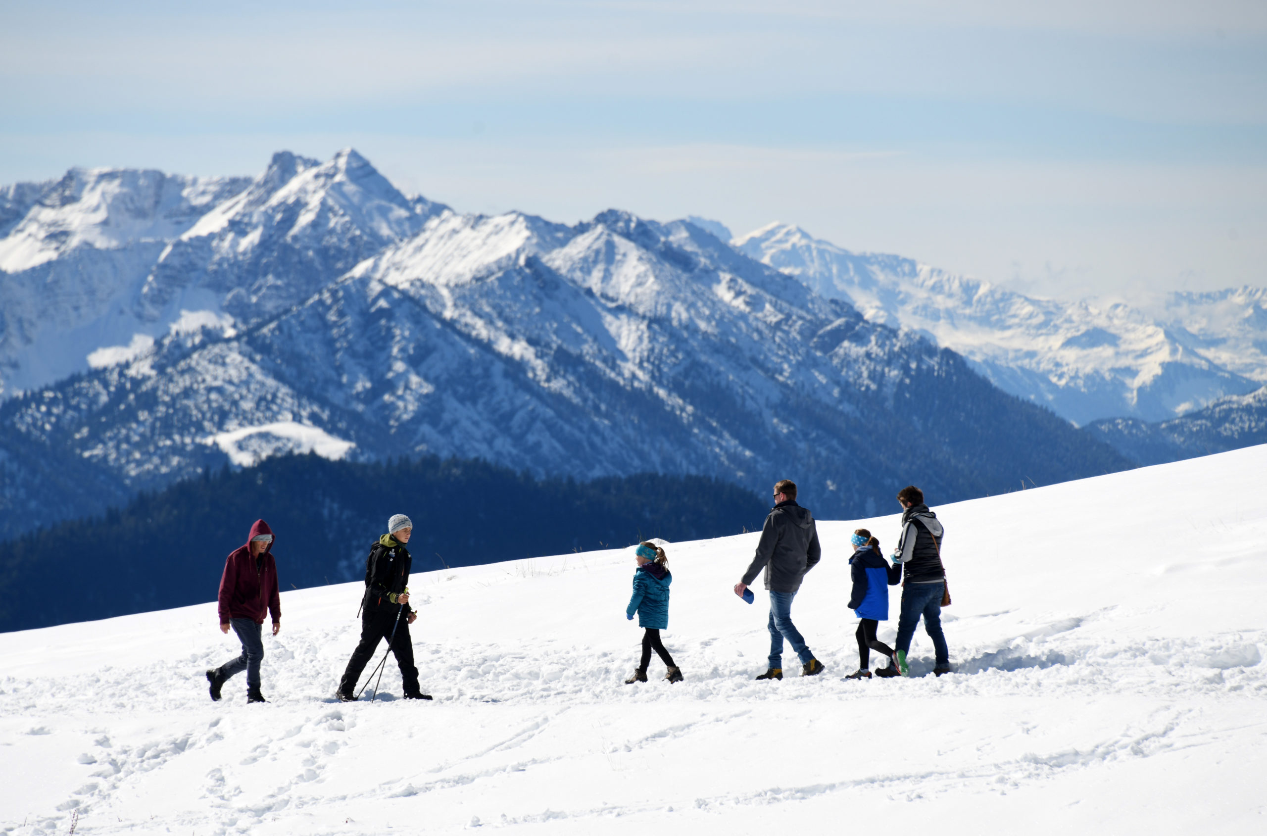 Hikers walk along a snow-covered hiking trail