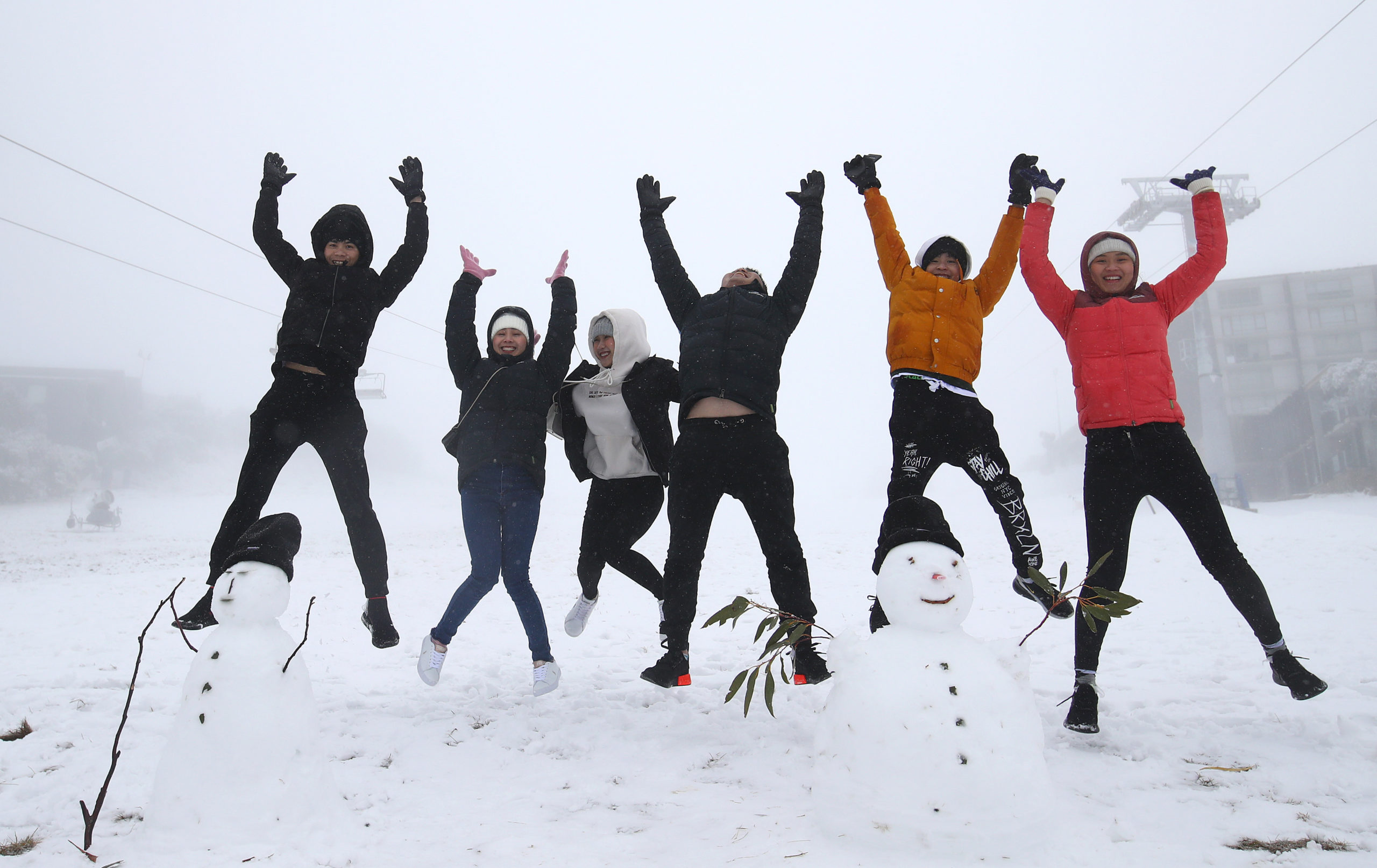 group of skiers jumping in air