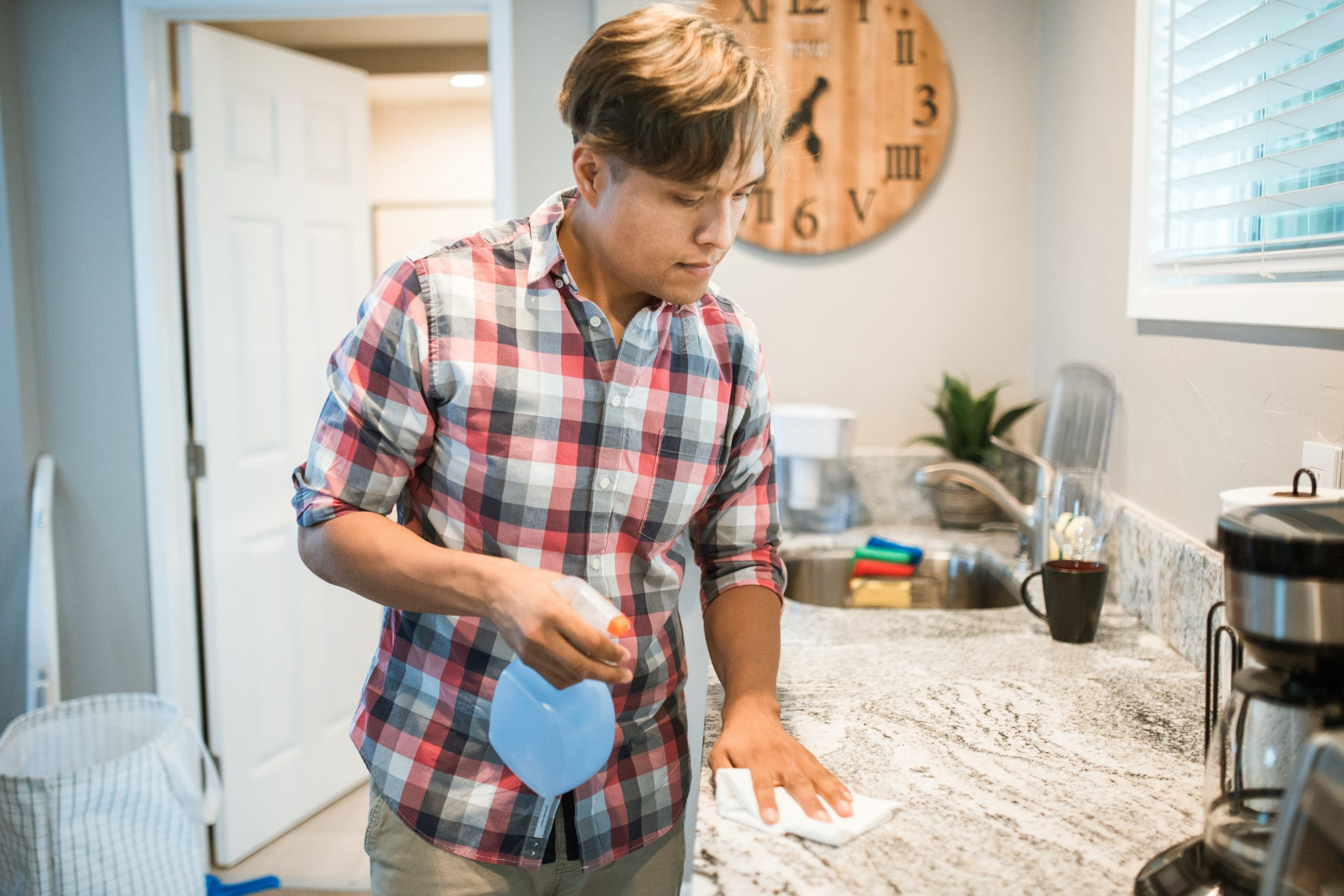 Asian man in checkered shirt washing a marble kitchen counter