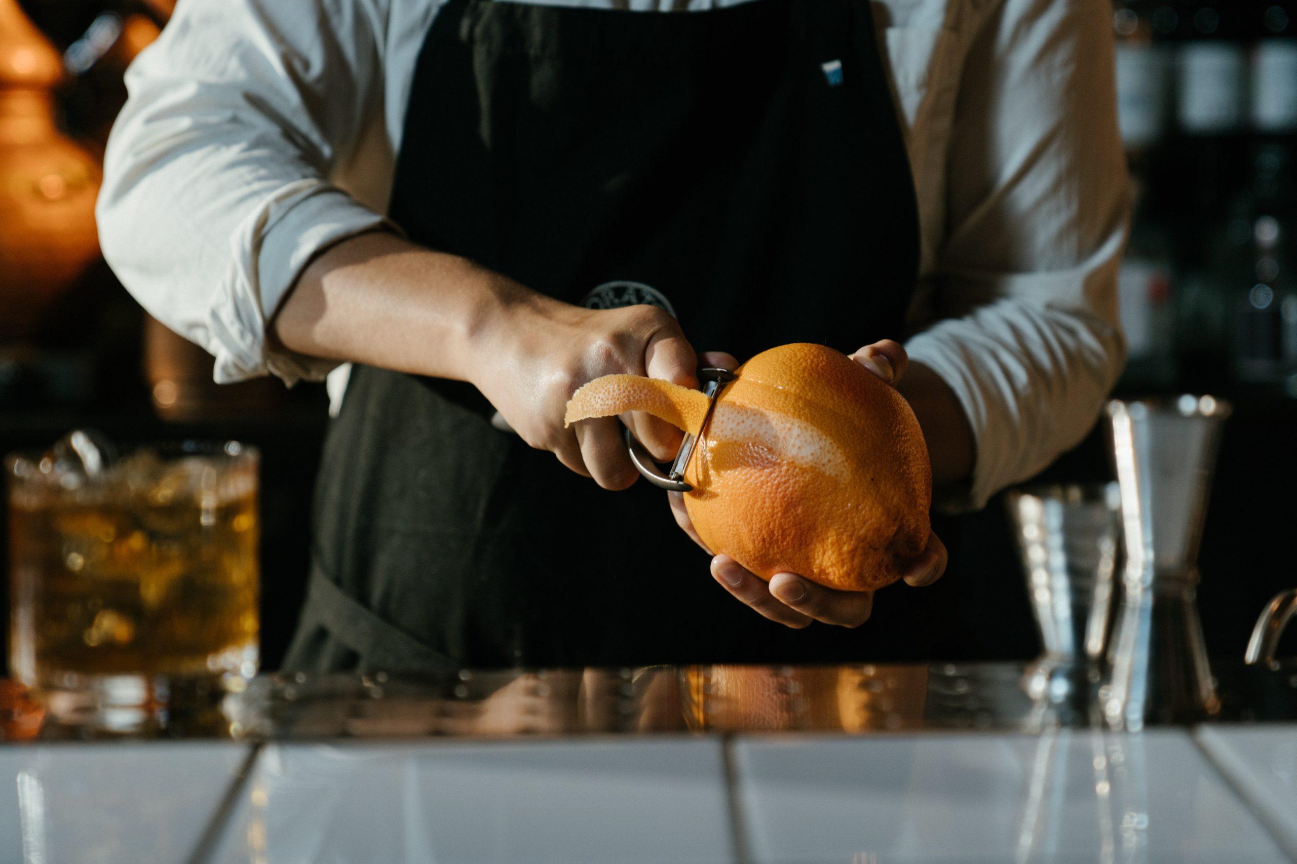 male bartender peeling orange zest in a bar