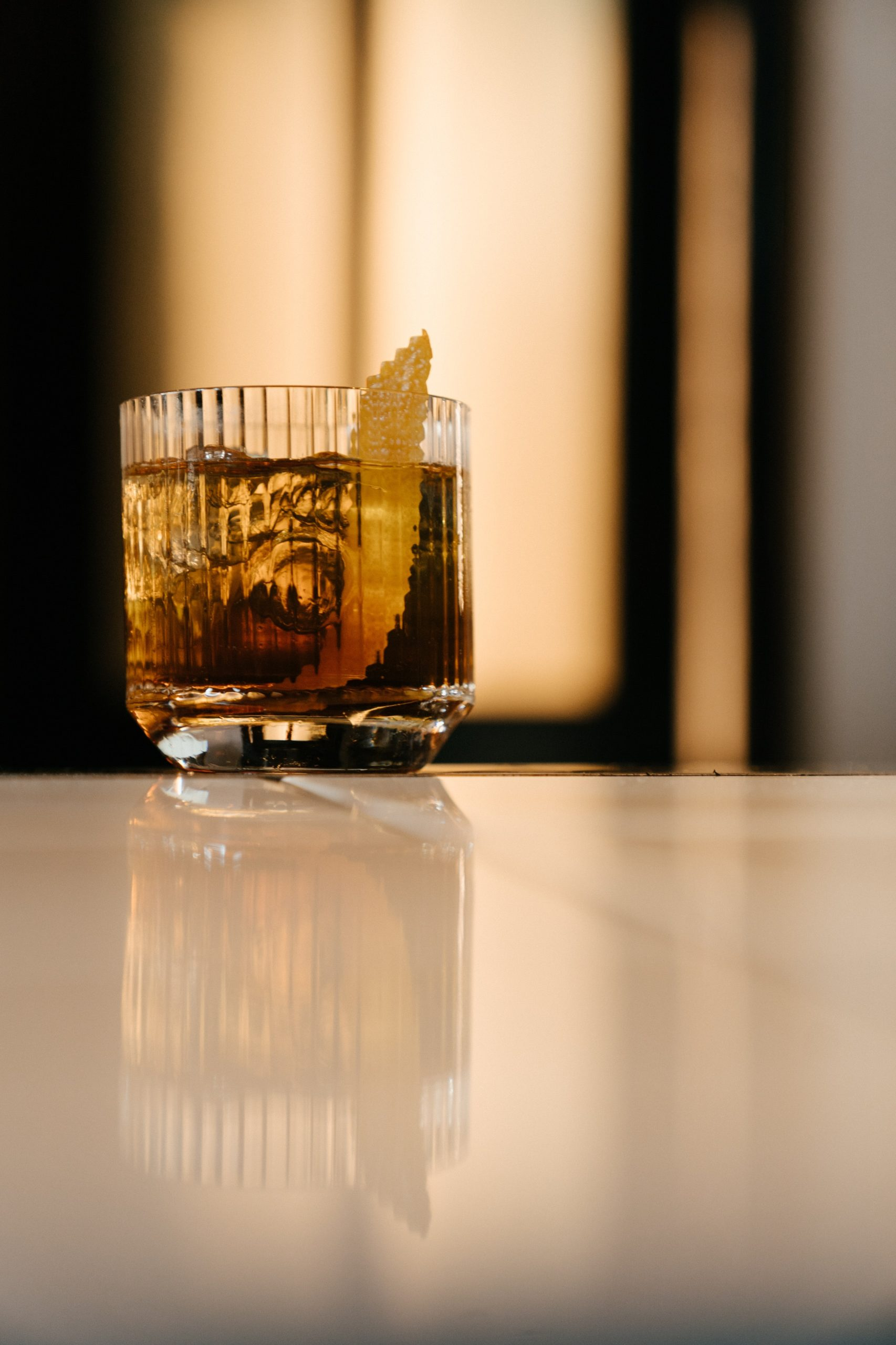 old fashioned whiskey drink in lined glass on a counter with garnis