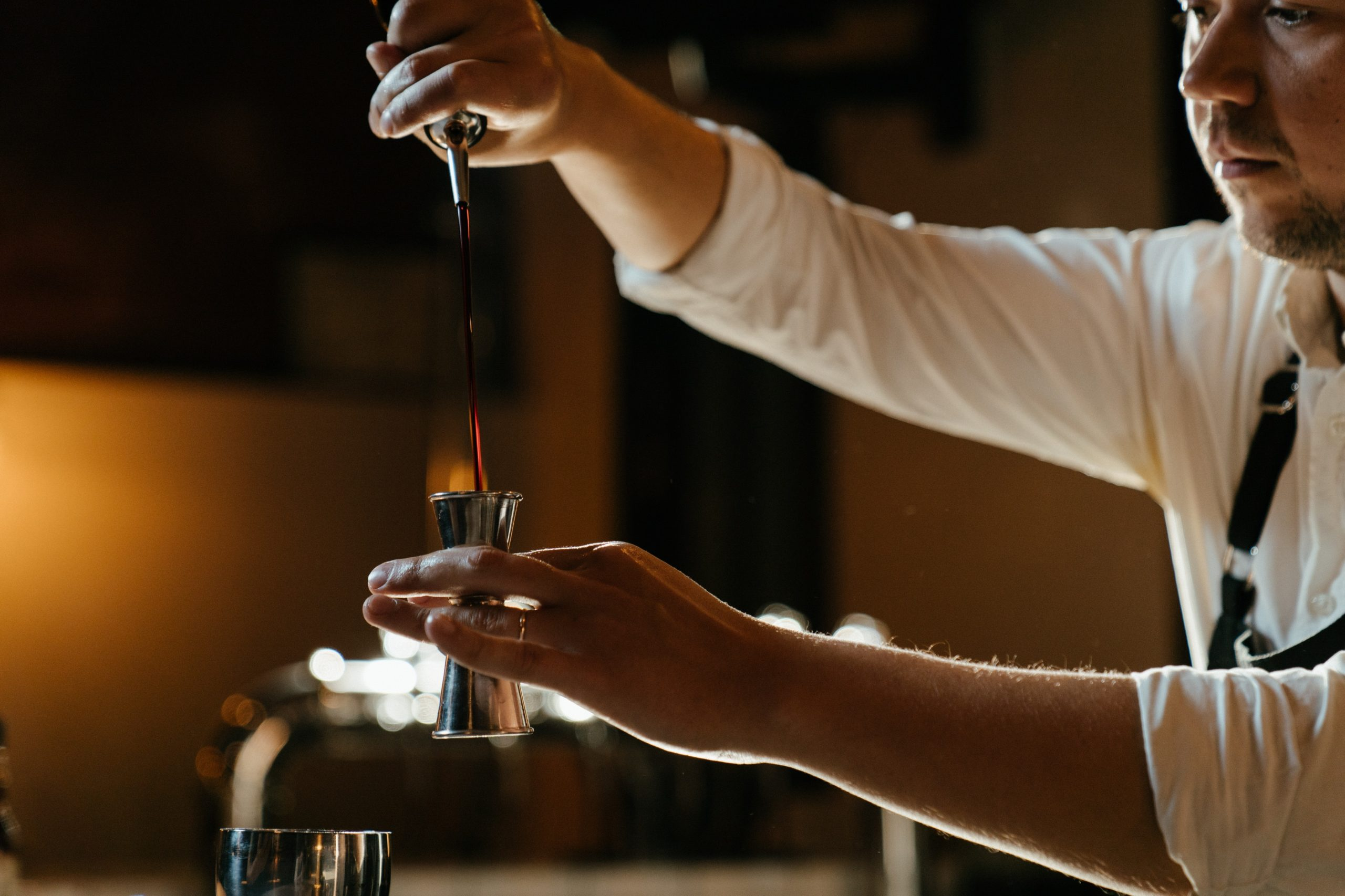 bartender pouring alcohol into a jigger in a bar