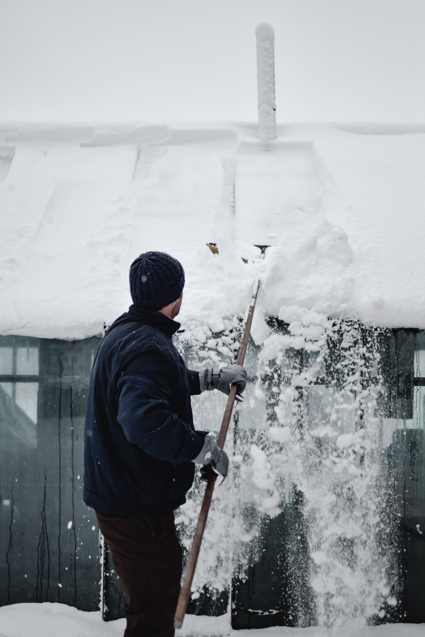 man in black coat and had brushing snow off of a shed roof in the winter