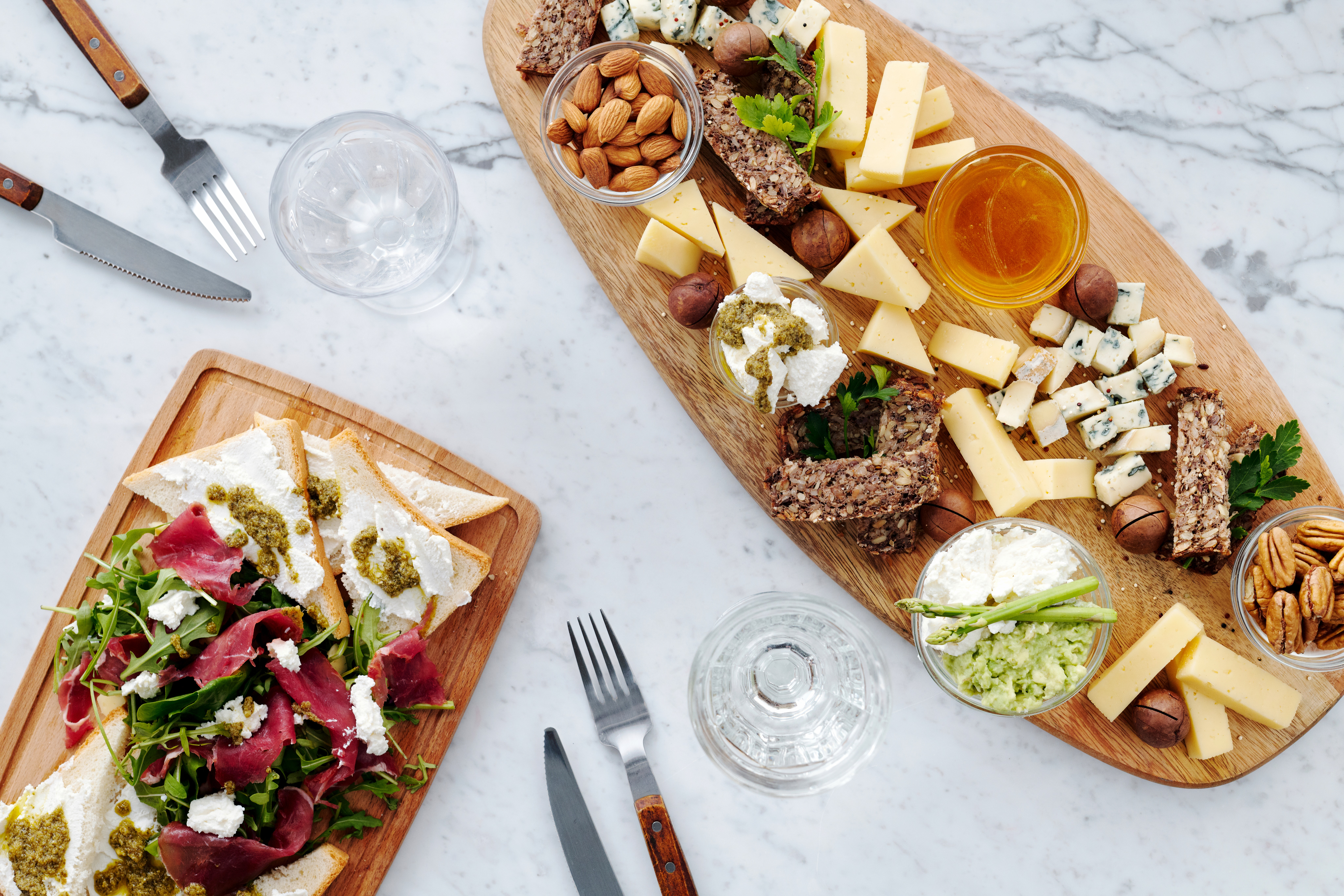 long oval charcuterie board filled with antipasto and deli items beside a rectangle wood board filled with meats, greens and breads