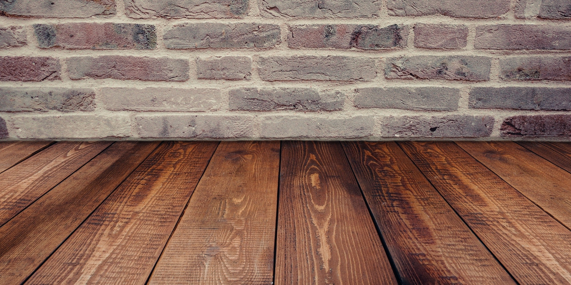 wide stained wood plank flooring against grey brick wall