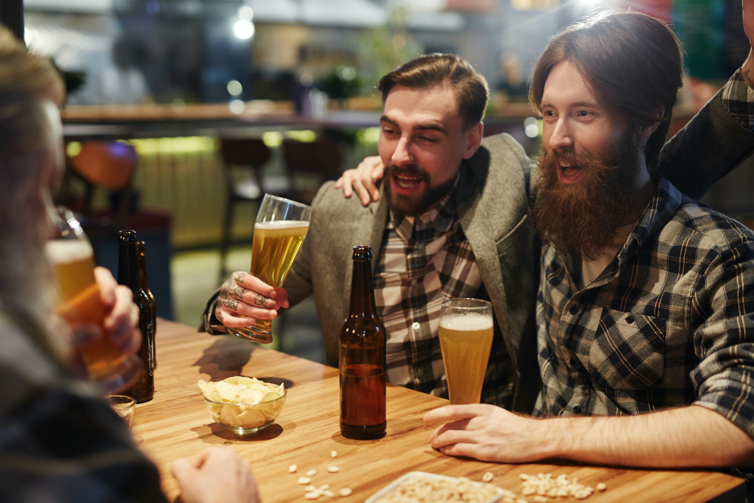 man with mustache and man with beard having a good time at a table drinking beer
