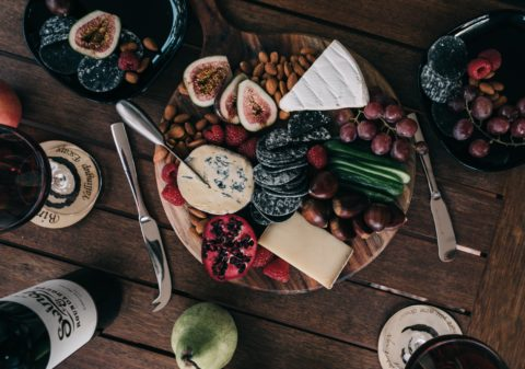 fancy cheese, crackers, fruit and nuts on a round serving tray seved on a rustic wood table with wine