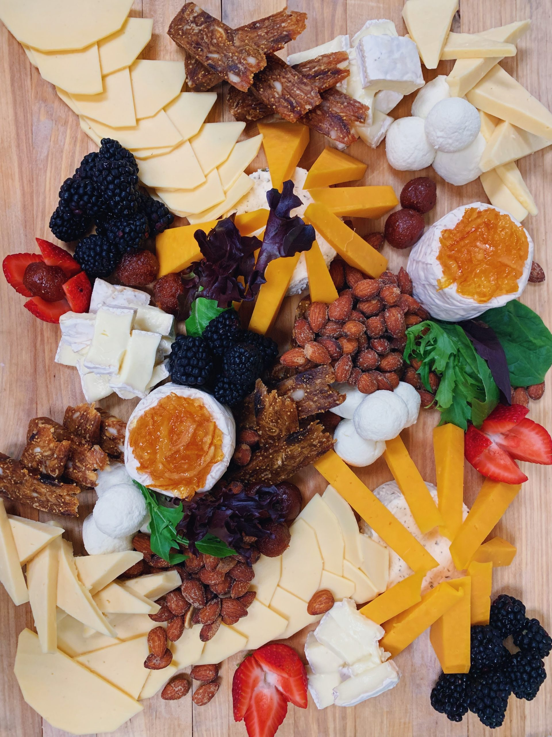 loaded and colorful platter of cheese, meat, fruit, candy peanuts and greens on a wood board