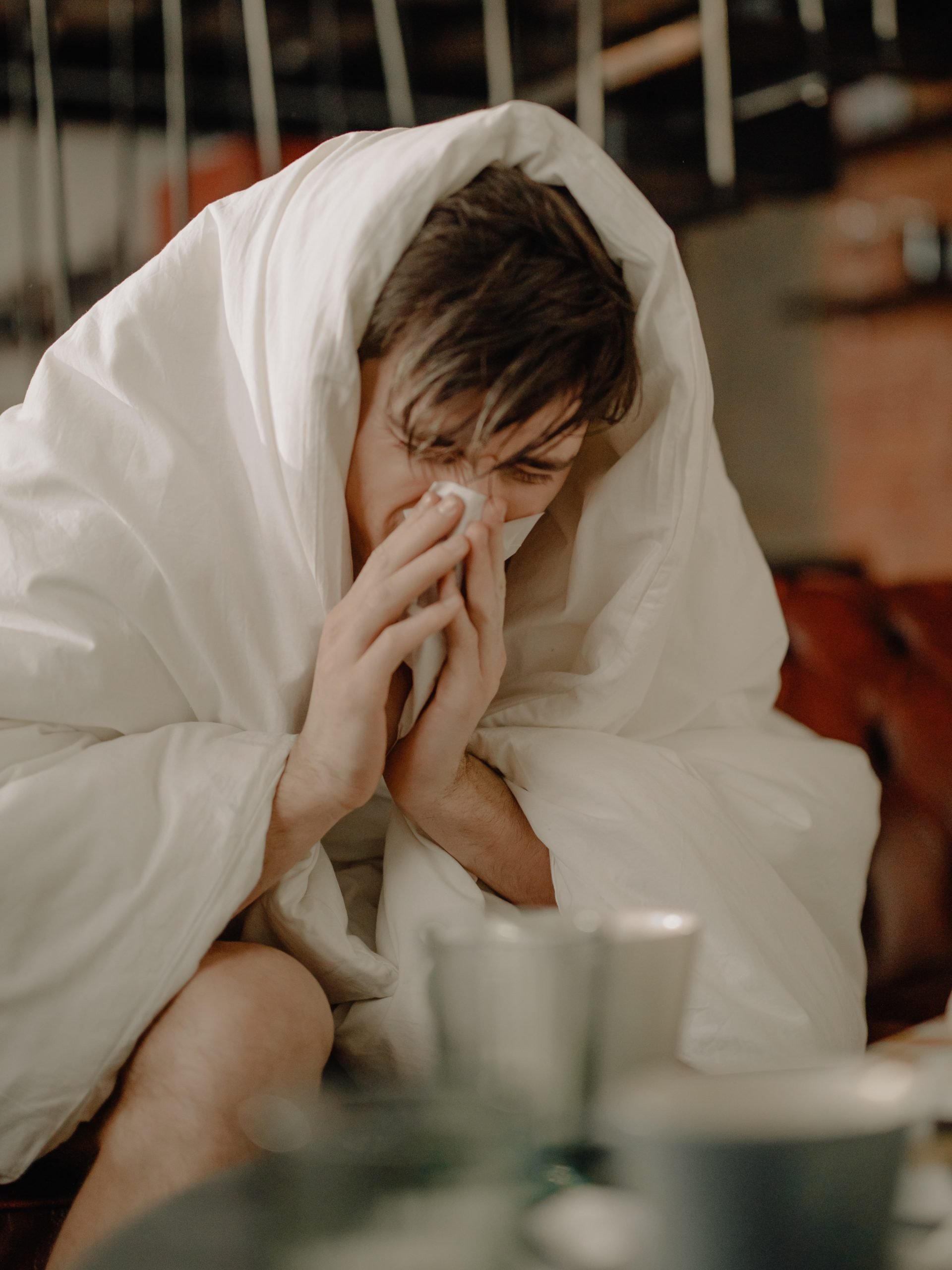 sick man wearing a blanket and blowing his nose