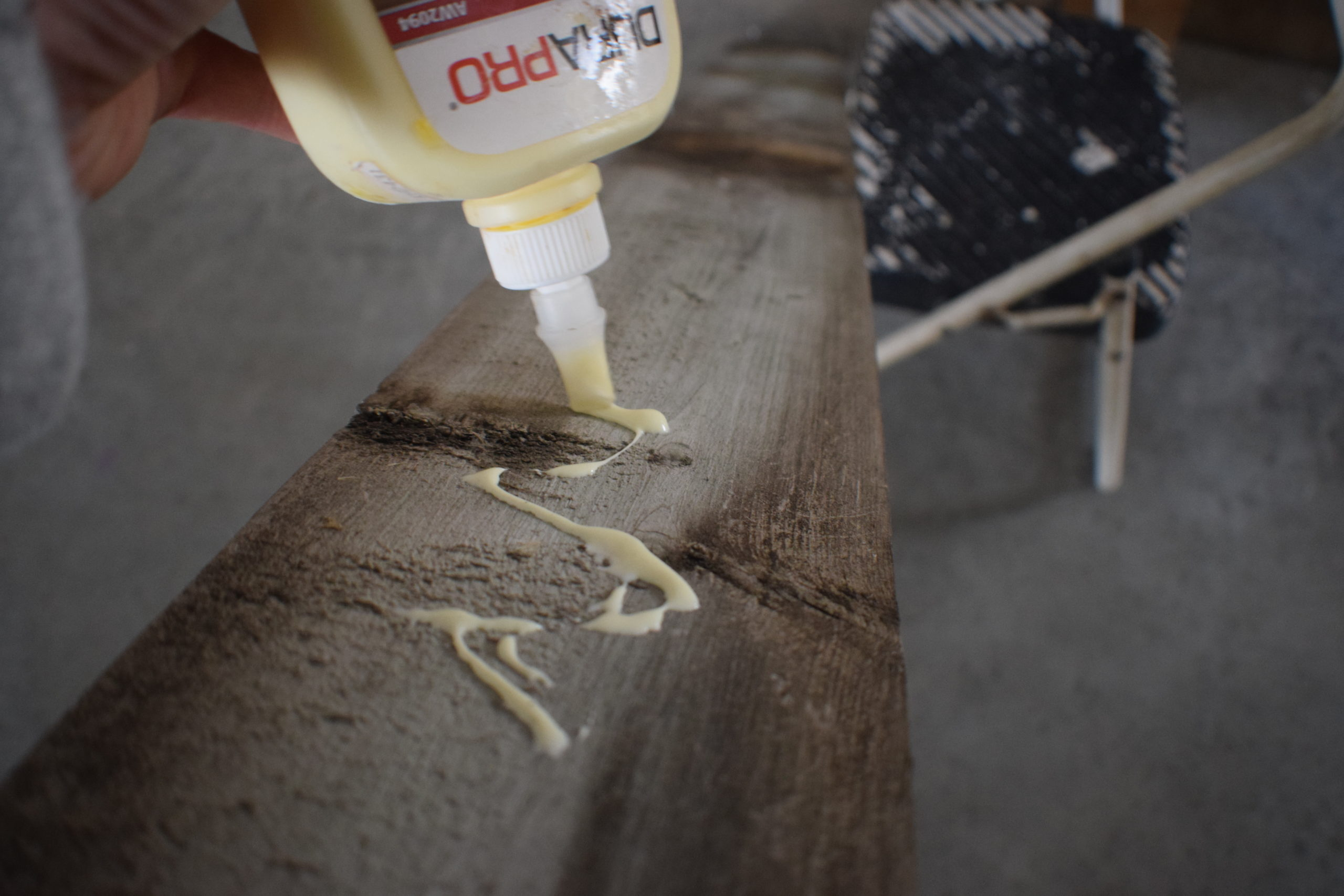 Wood glue being put on the back of a board in zig zag motion