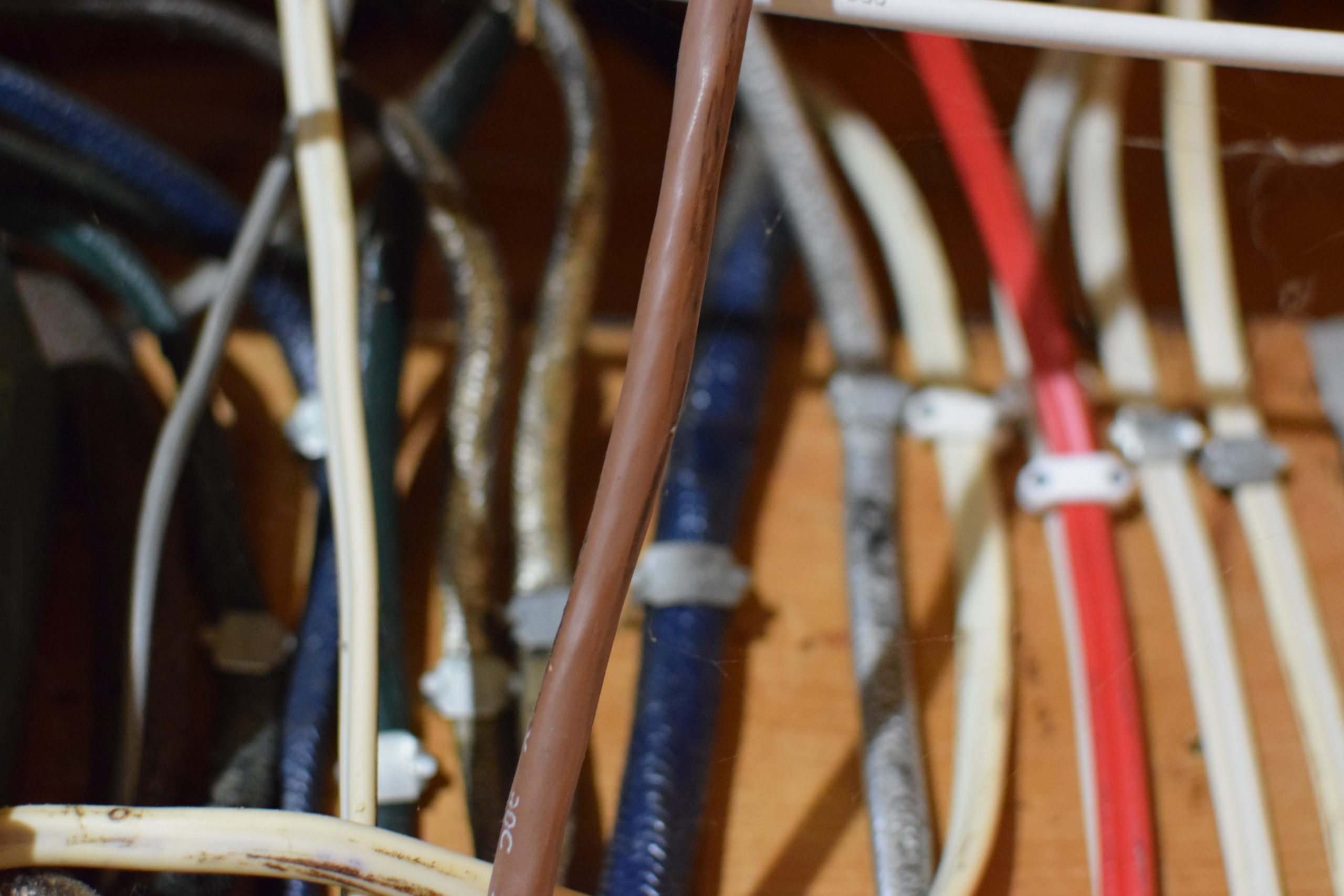 red, white, blue, brown and silver vertical electrical wires in utility room