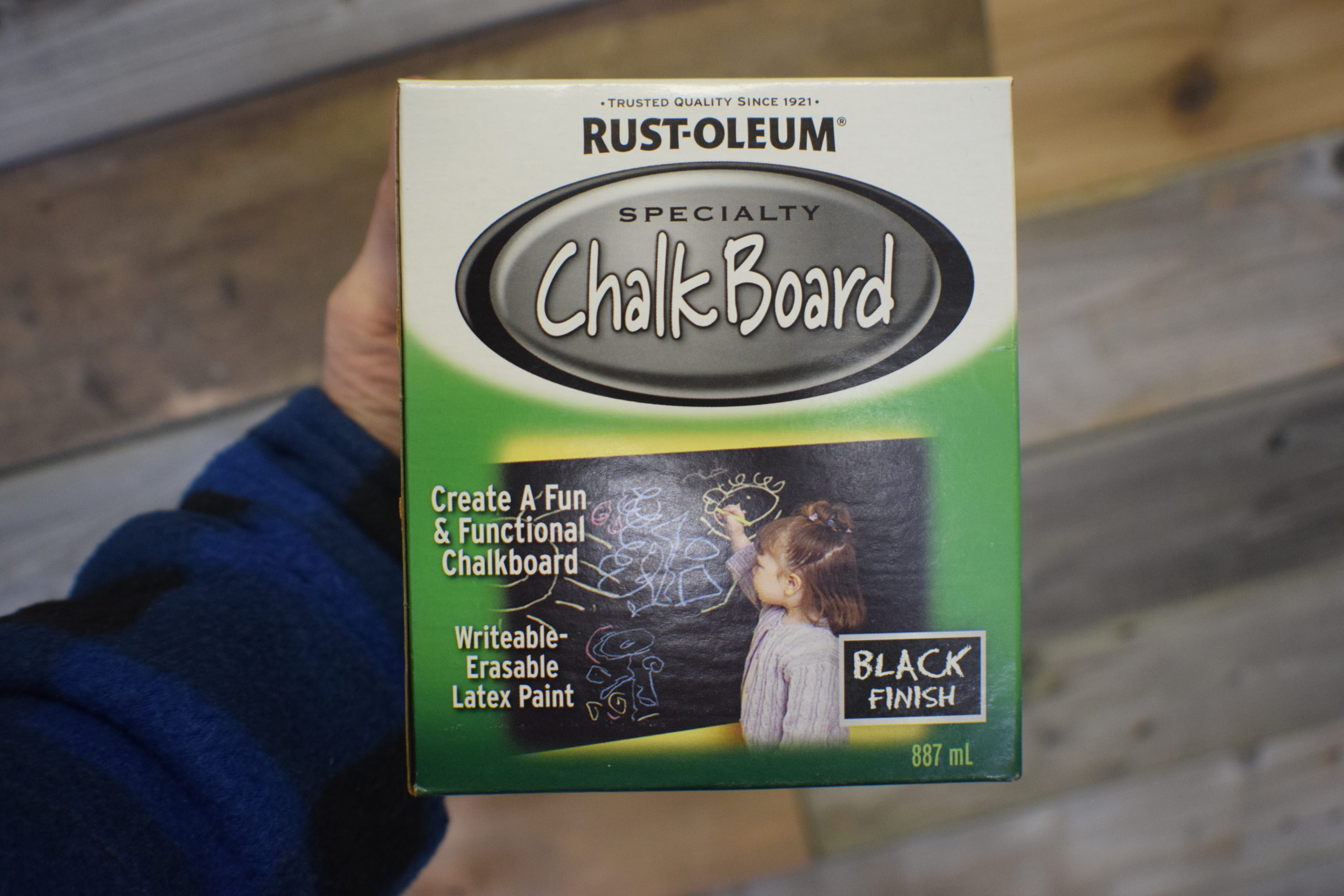 Box containing Rustoleum specialty Chalk Board paint in hand