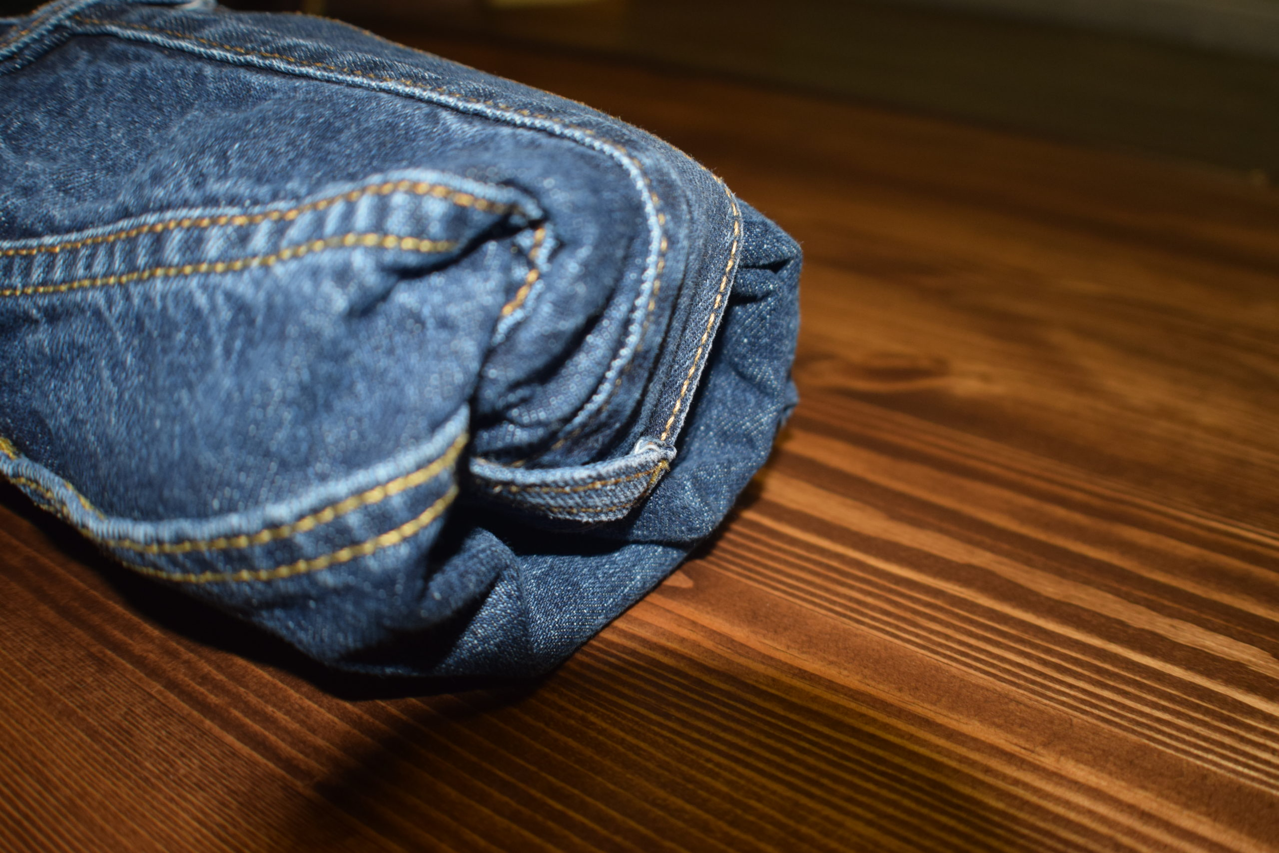 pair of blue jeans rolled up on a wood surface