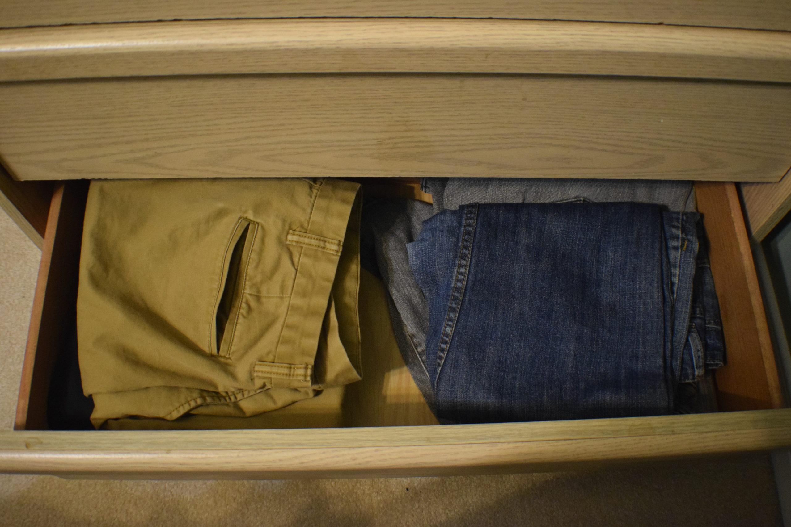 folded pants in a bottom drawer of a light wood dresser
