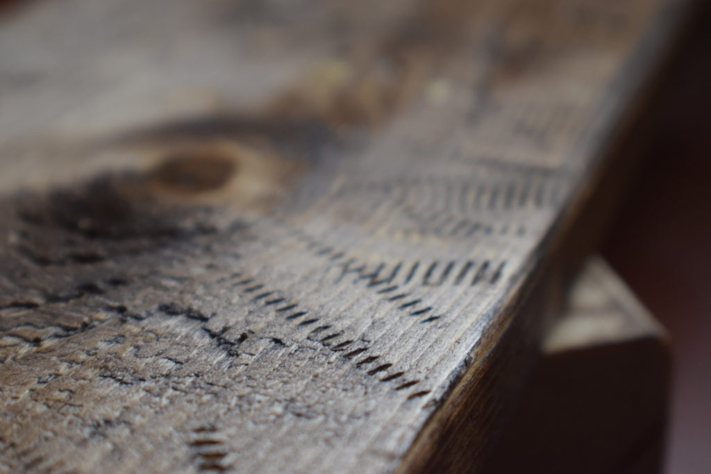 Weathered wood with screw markings stained brown