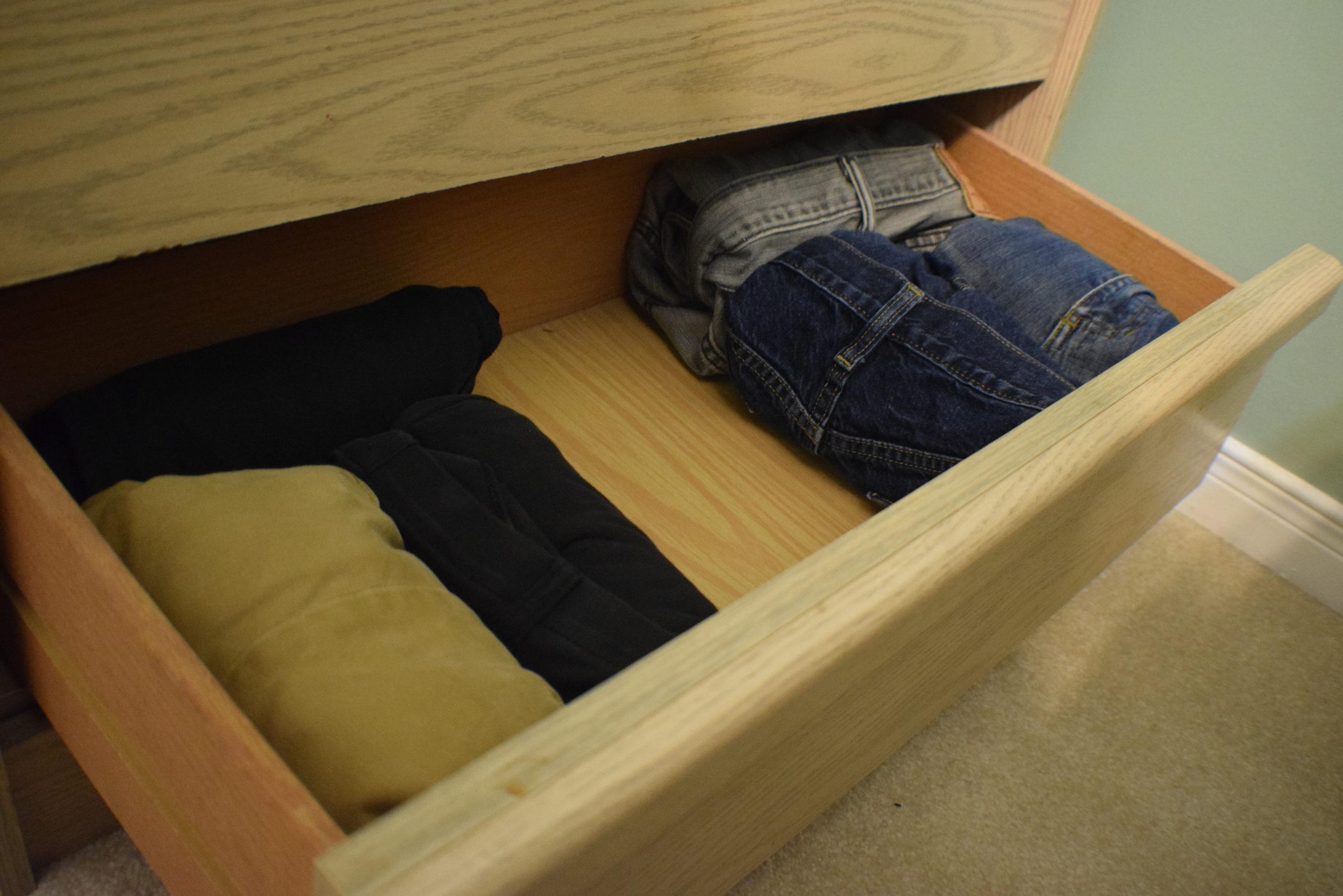 rolled pants in bottom drawer of light wood dresser