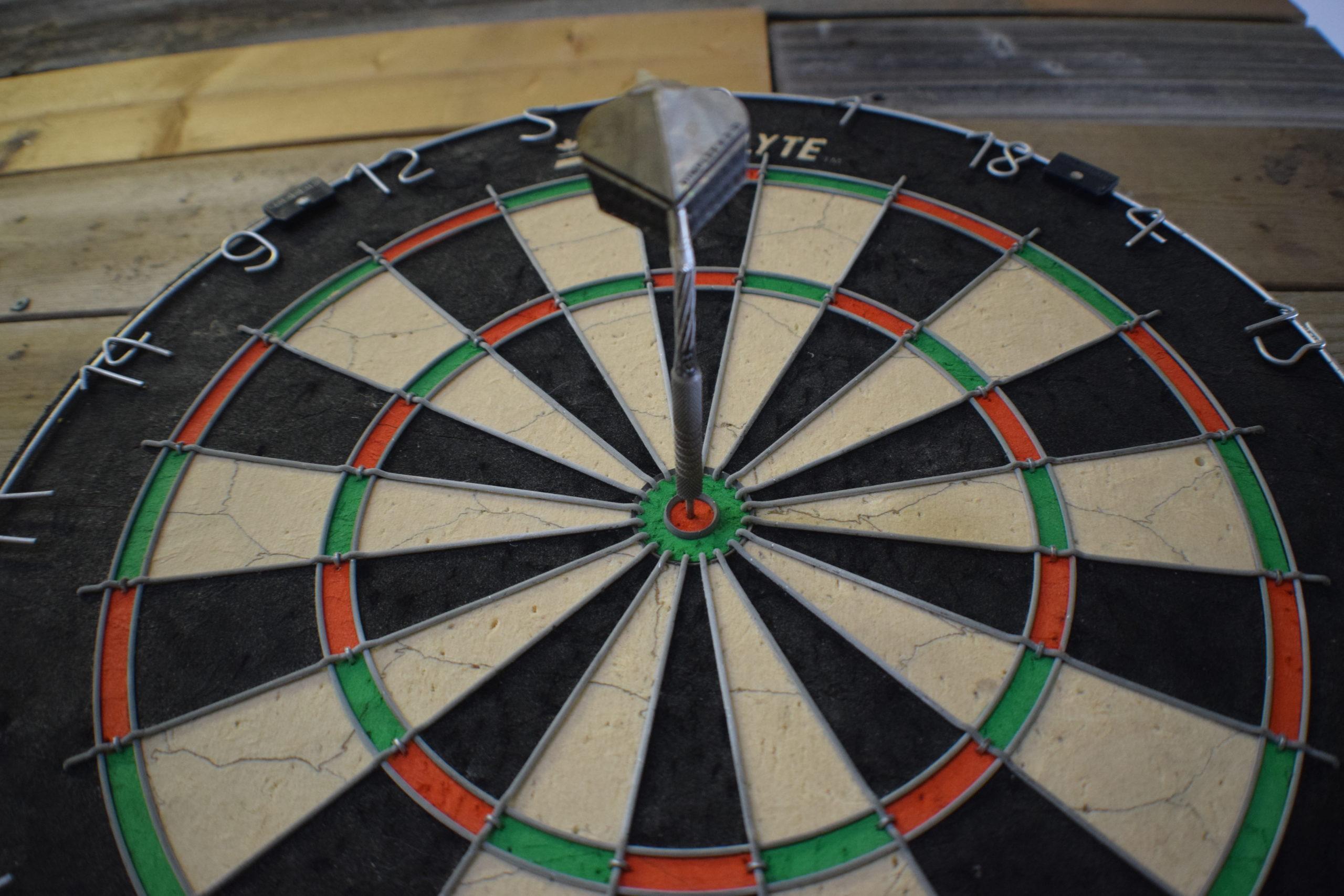 standard dartbaord on wood wall with dart in the bullseye