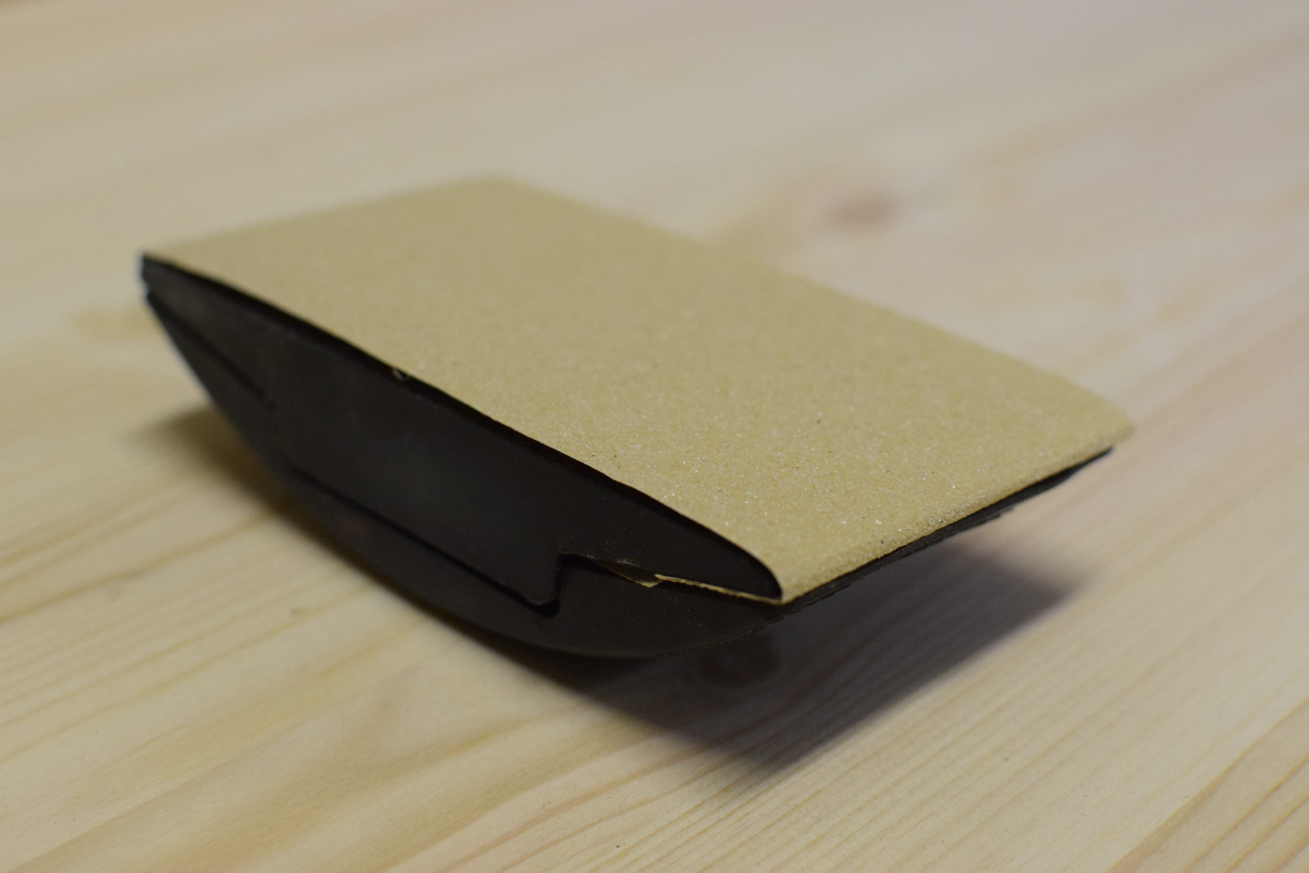 hand sanding block loaded with sand paper on a pine surface