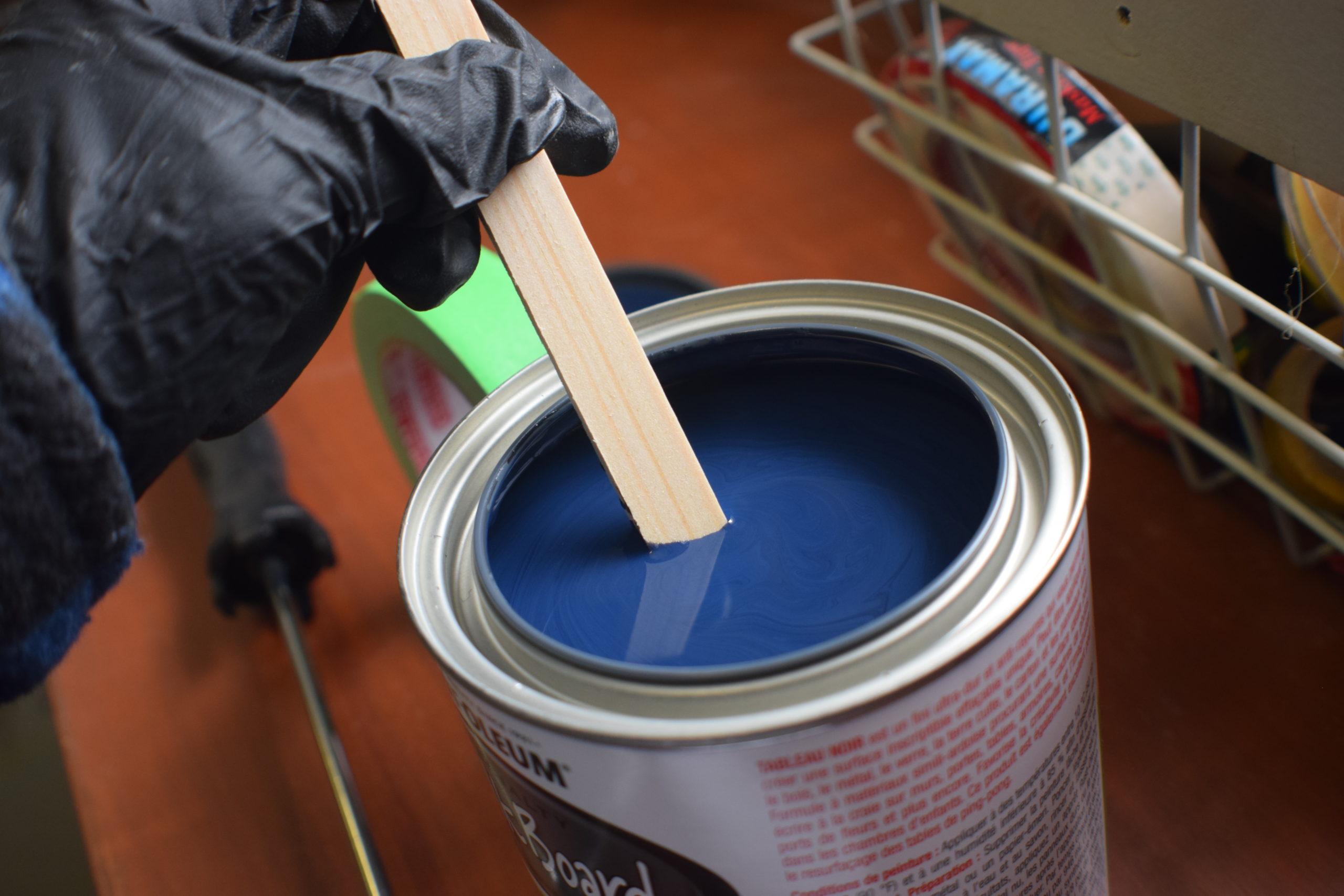 Hand with black glove stirring a can of rustoleum chalkboard paint