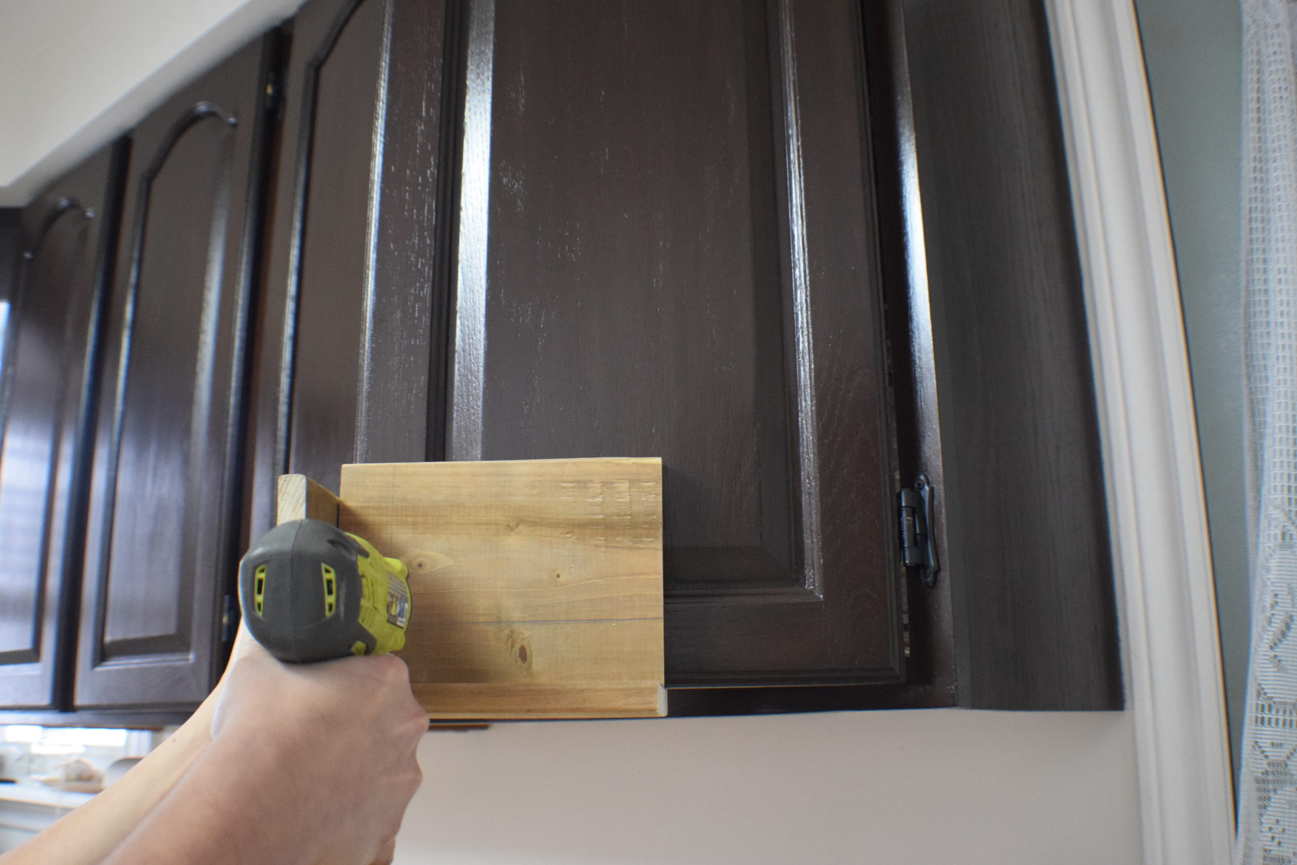 drilling through a wood jig on a kitchen cabinet door