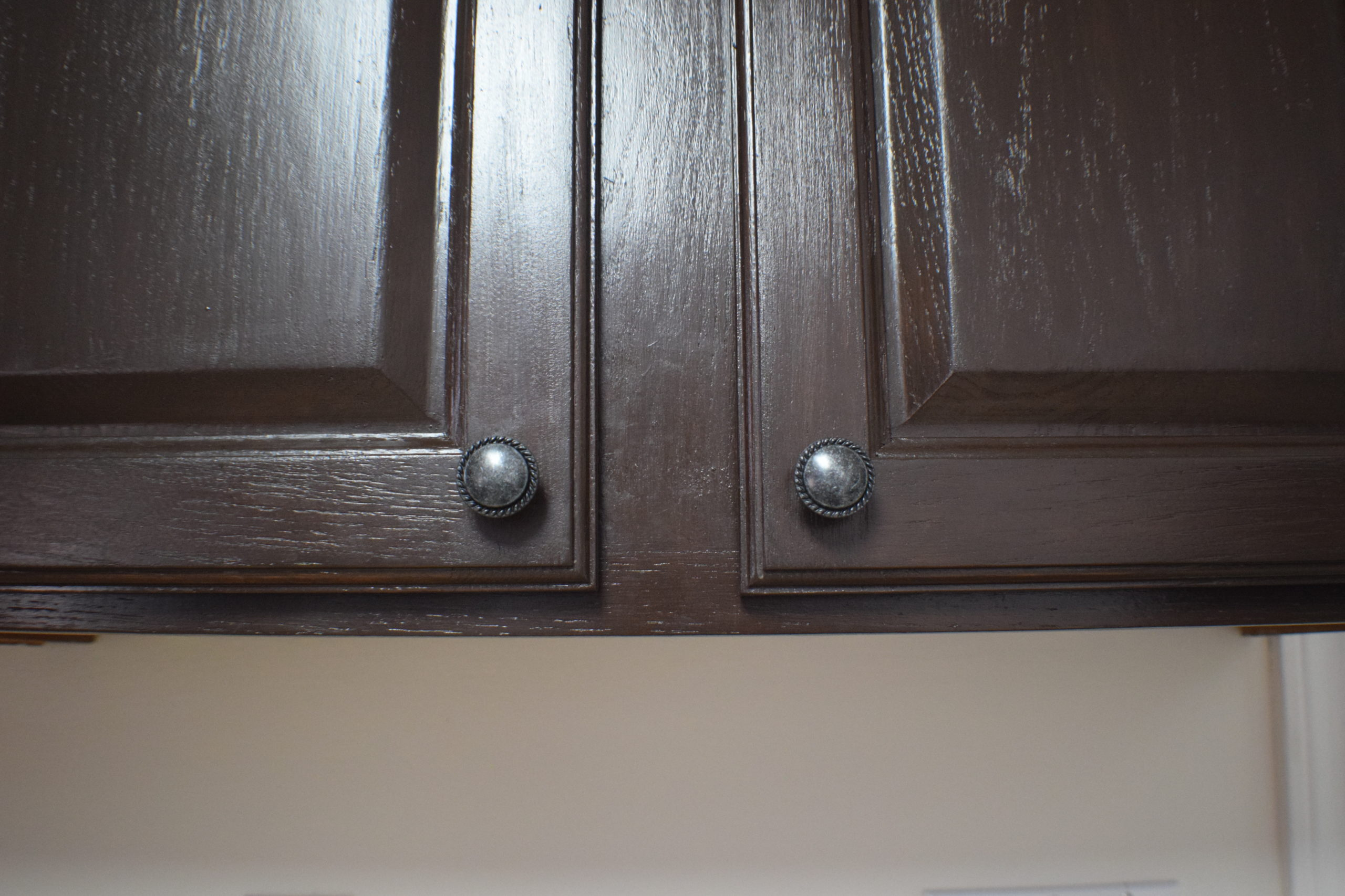 dark stained cabinet doors with new handles