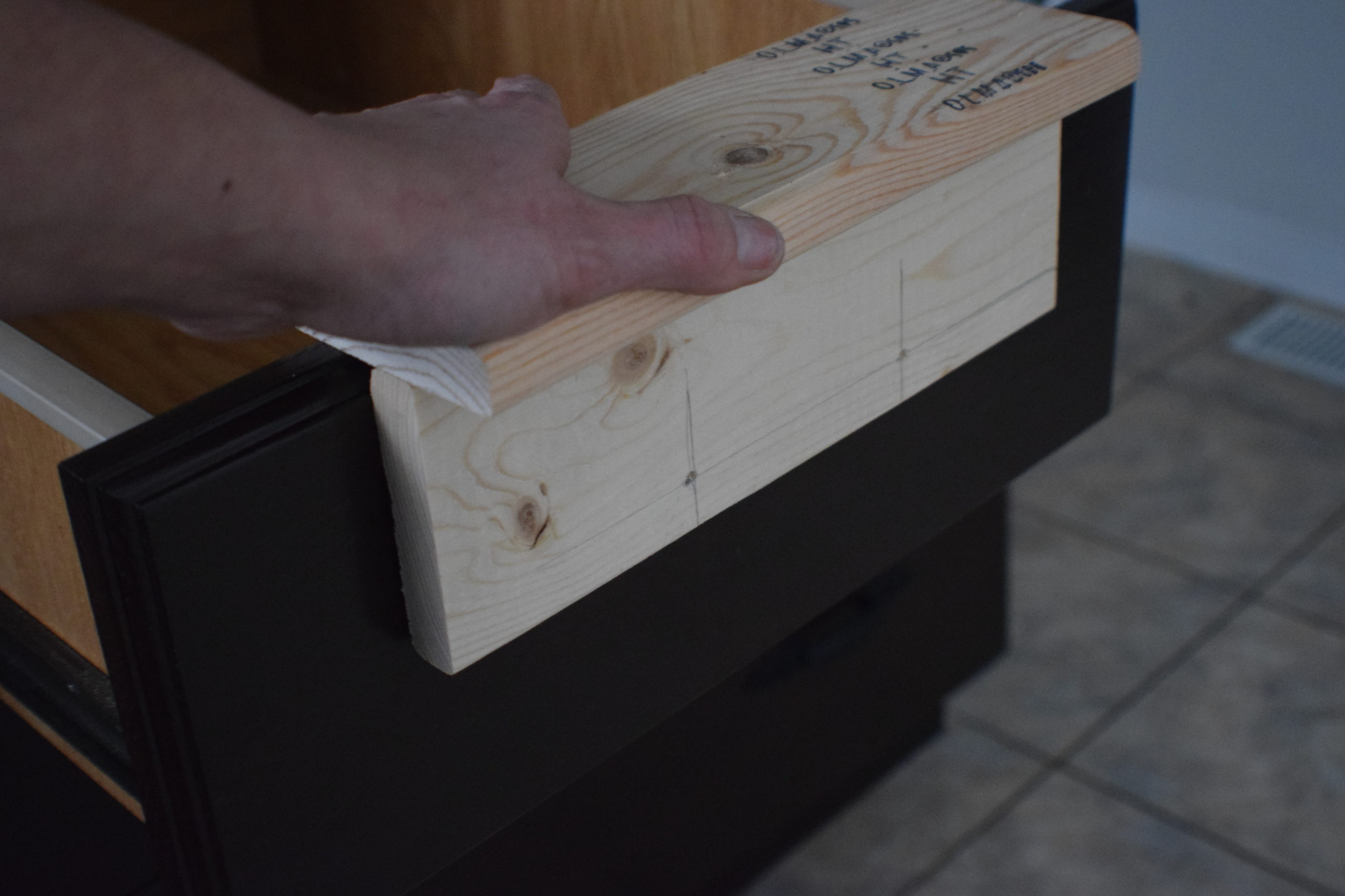 A cabinet drawer jig in place on a dark drawer