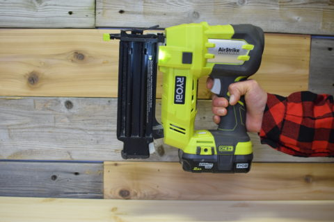 hand holding green and black Ryobi airstrike nail gun on a wood background