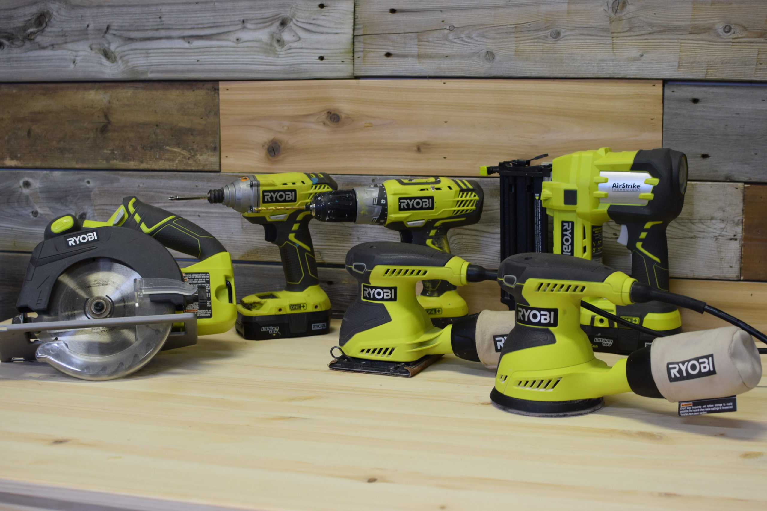 group shot of Ryobi tools on a wood table against rustic wood background