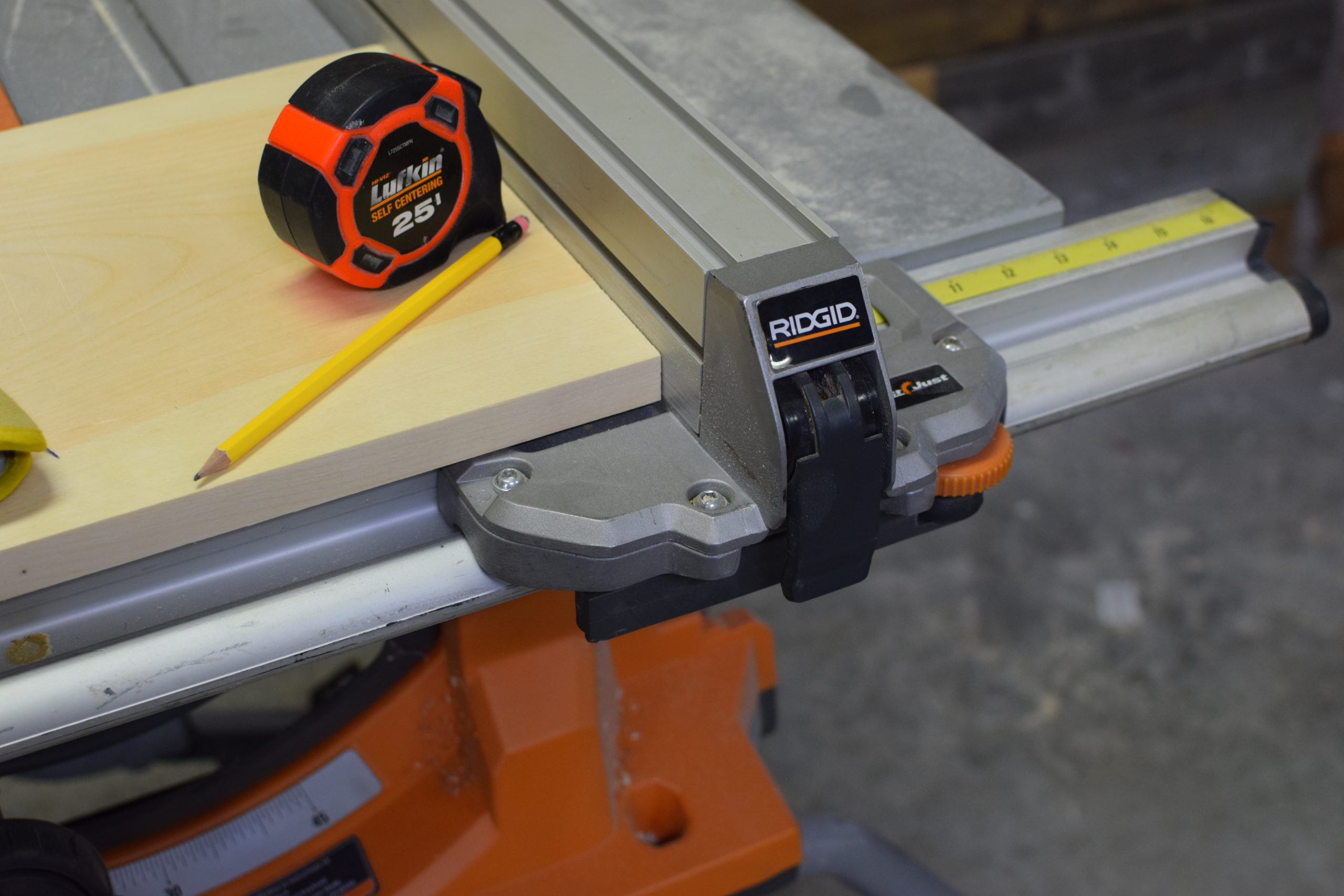 tape measure and pencil on top of wood on an orange table saw