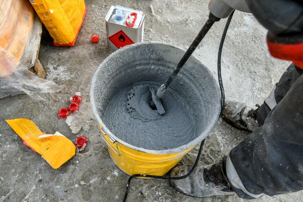 worker mixing concrete in bucket