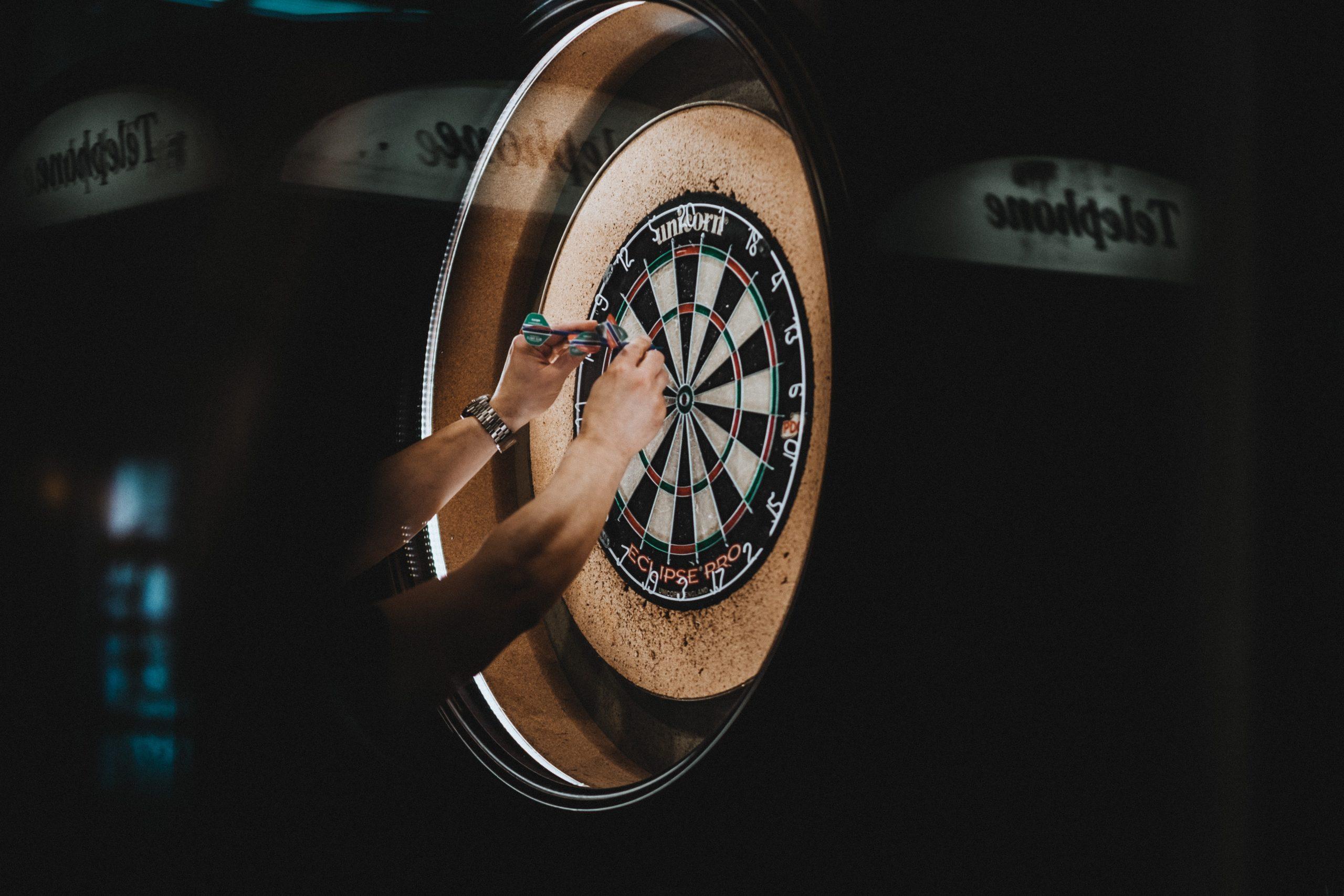 hands grabbing darts from dart board in dark room