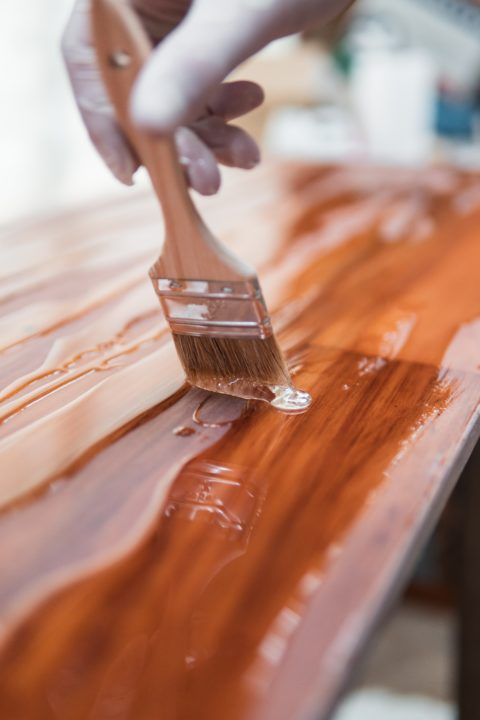 using a paint brush to apply stain on wood
