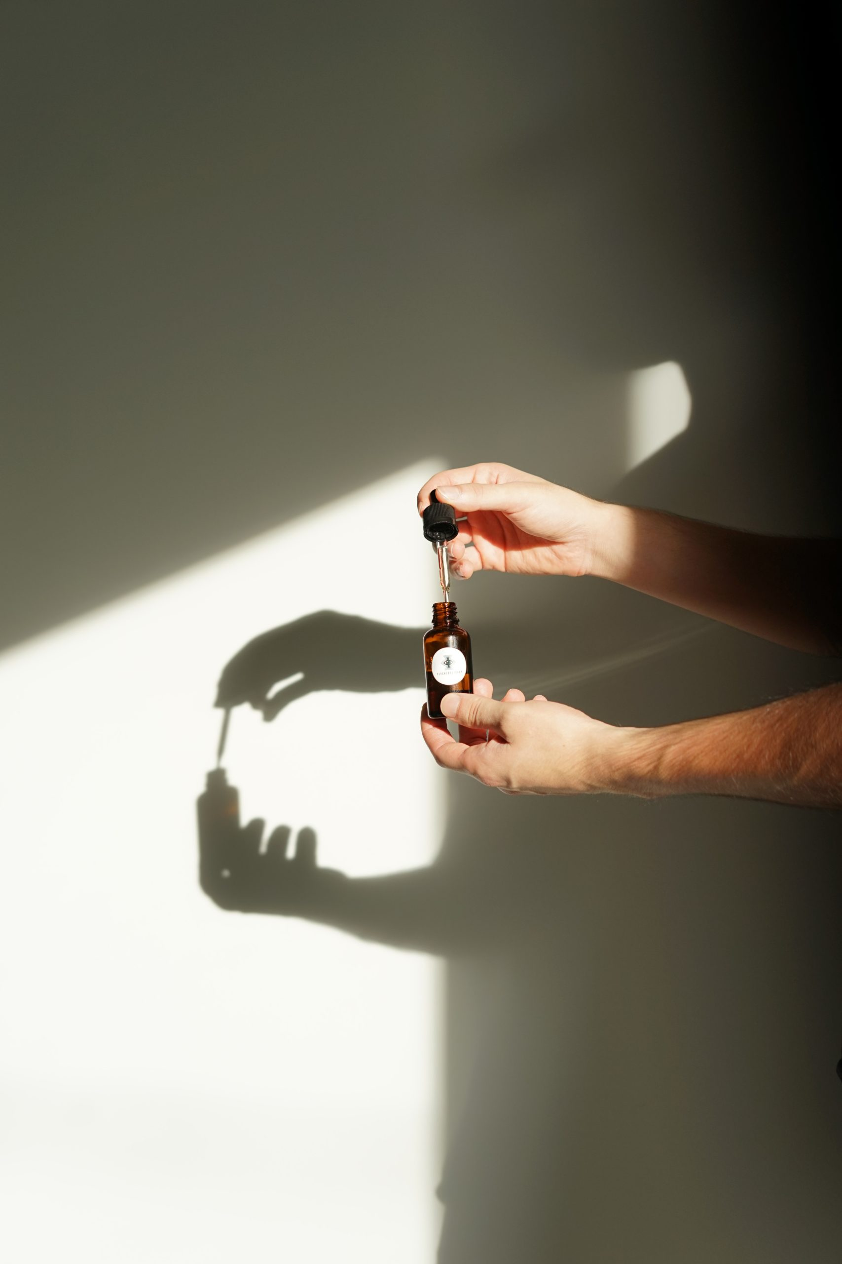 man hands holding a bottle of essential oil in front of a wall with a shaddow